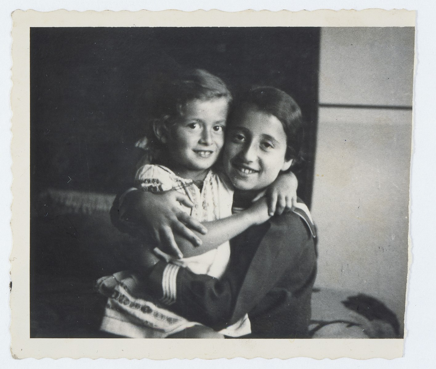 Lida Kleinman hugs an older girl, Ola Weinberger.