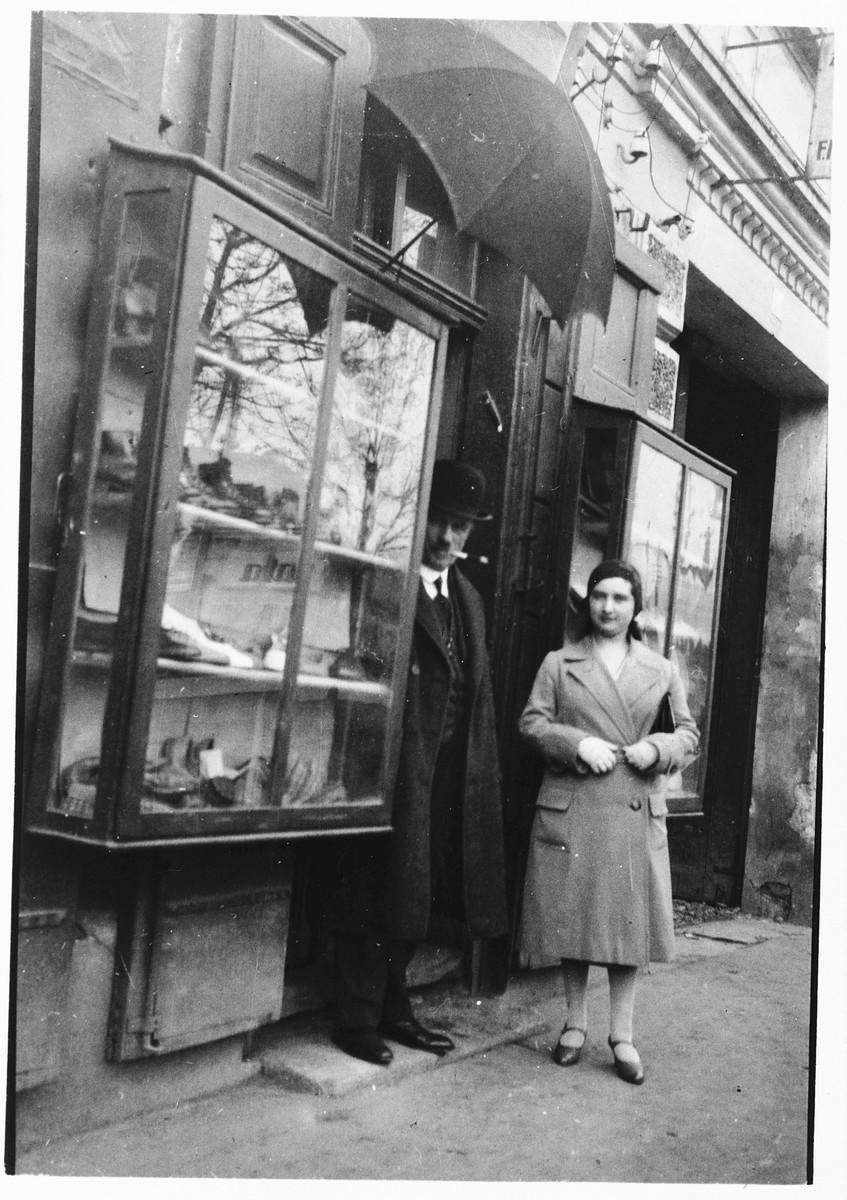 Jozsa Kovacs (later Taubner) stands next to her father Alexander Kovacs in front of the entrance to a store in Galanta.
