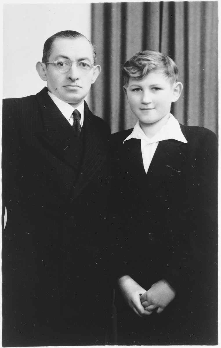 Studio portrait of a Jewish father and son taken on the occasion of the son's bar mitzvah, two years after the liberation.  Pictured are Arie and Henri Donner.
