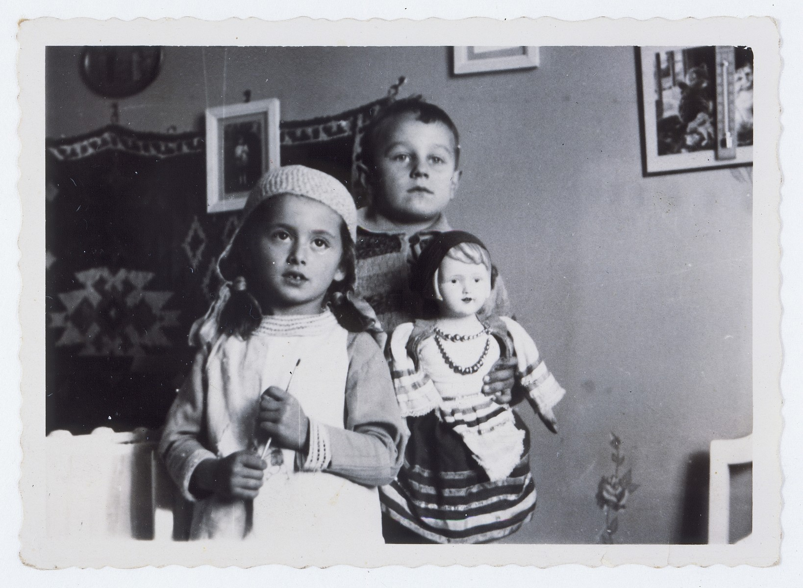 Two young children play with a large doll.  Pictured are Lida Kleinman and Jezek Pepelowier.