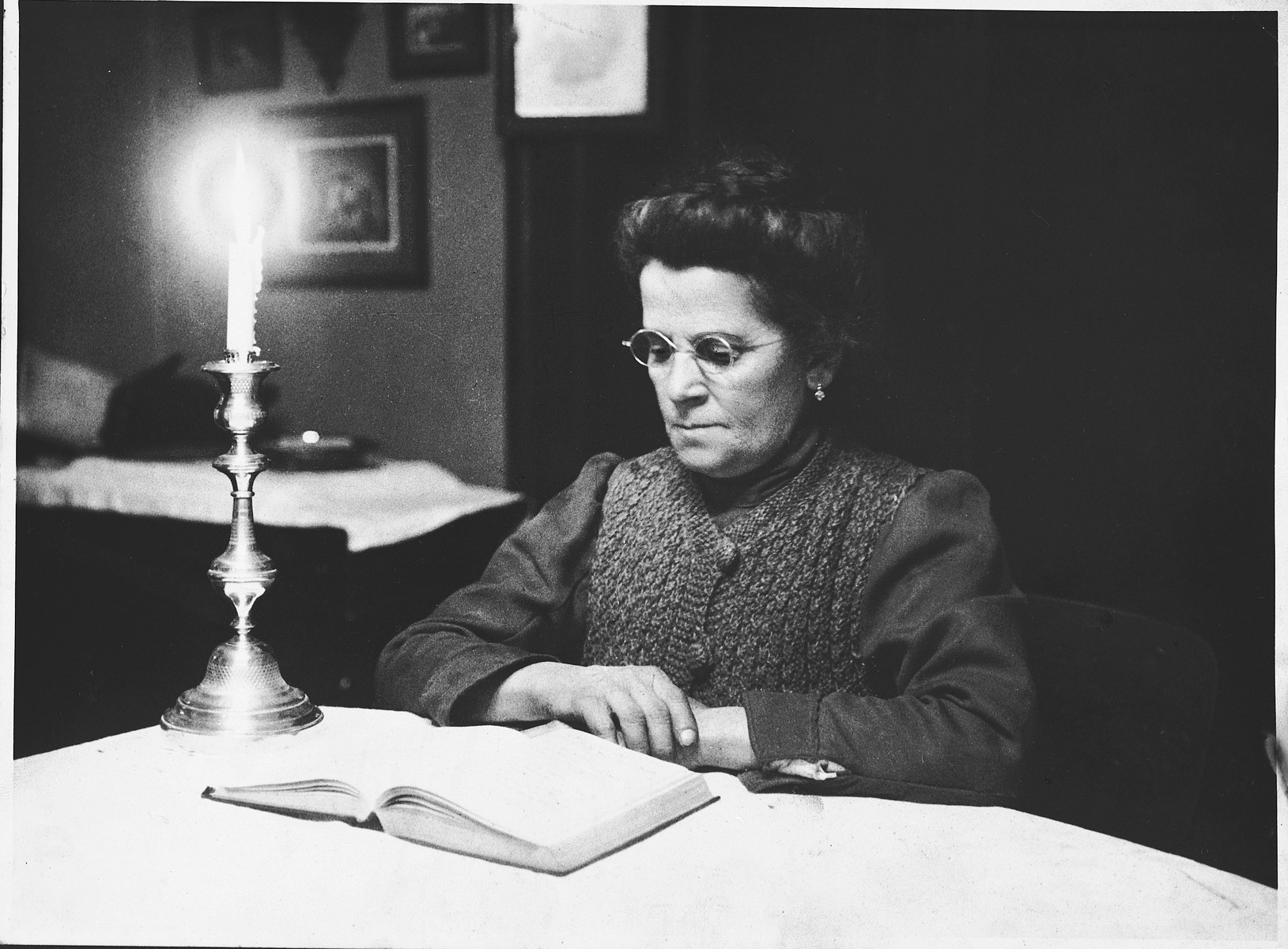 Close-up portrait of Katie Taubner (grandmother of the donor) reading a book by candlelight.
