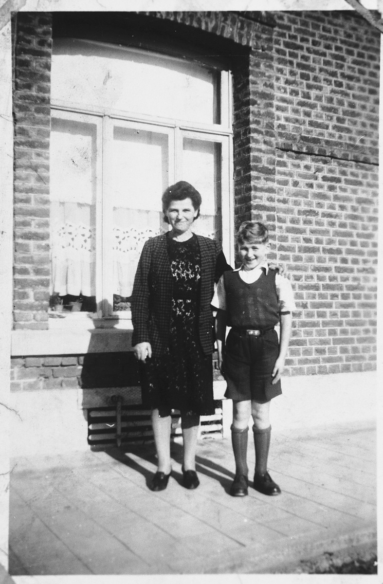 A Jewish mother and son who are living in hiding in separate locations in Belgium, pose together outside his rescuers home in Dinant, Belgium, where she has come to visit for his tenth birthday.  Pictured are Sabine and Henri Donner.