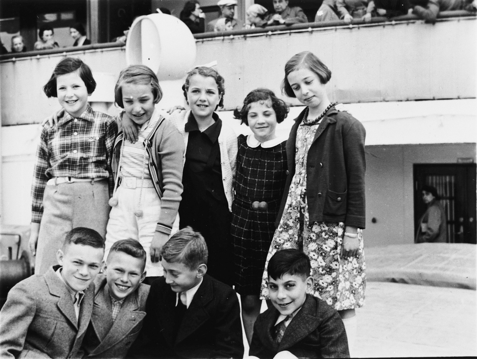 Group portrait of Jewish refugee children on board the St. Louis.   Among those pictured are Evelyn Klein (back row, center), Herbert Karliner (front row, left), Walter Karliner (front row, second from the left), and Harry Fuld (first row, far right).
