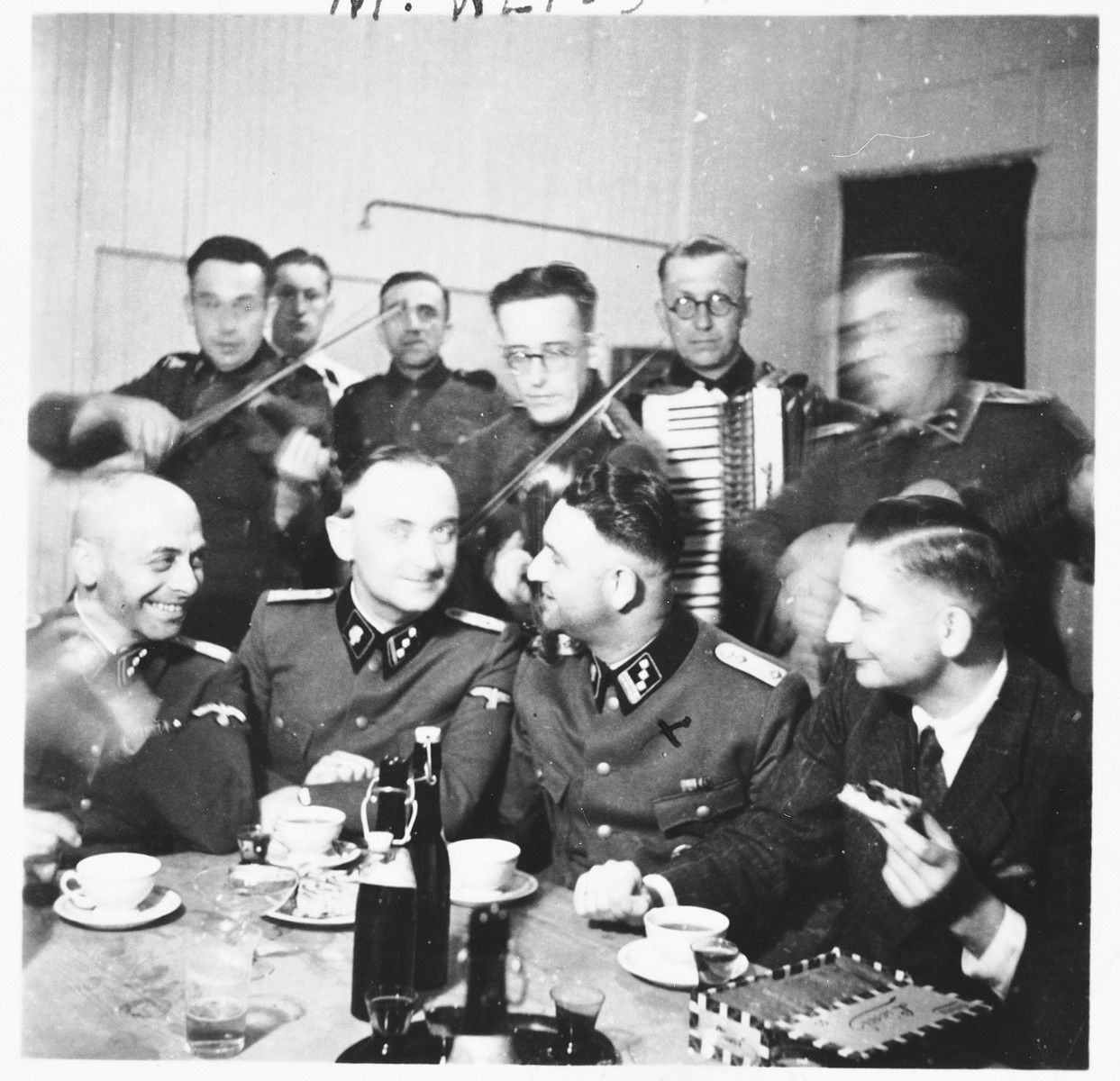 A group of SS officers gather together for a celebration [probably in Dachau].  Pictured sitting second from the right is Martin Gottfried Weiss.