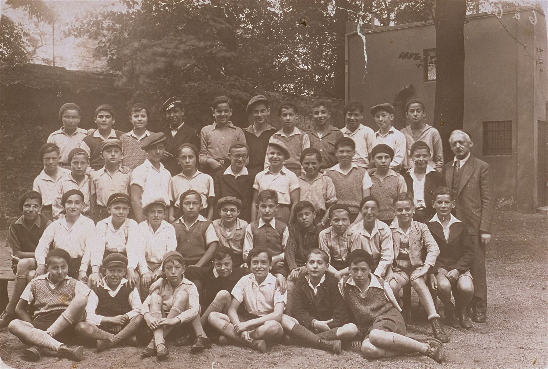 "Group portrait of students at the Adas Israel Jewish religious school for boys in Berlin.  Pictured in the front row, left to right are: unknown, Lotar, Halbersztadt, Engelhart, Halle, Petranker and Jacobi;  second row:  Roseman, unknown, Blecher, Manfred Barkowski, unknown, Birenbaum, Levy, Abraham Muhlbaum, Siegelman; third row: Kempe, unknown, Felder, Weil, Goldwasser, unknown, Walter Barkowski.  On the extreme right is the teacher, Halberstadt.  Second from the right in the last row is: ""Bombe"" Feldman, unknown, ""Negus"", Markus and Naftali."