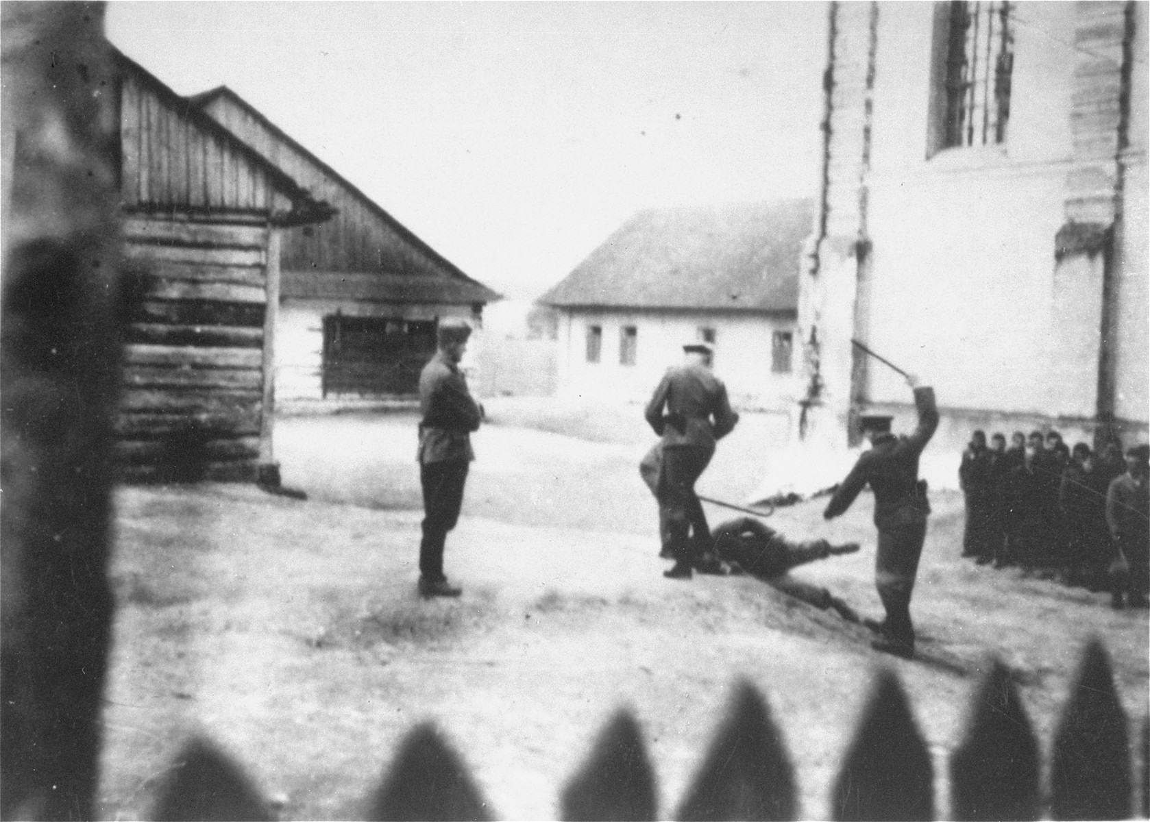 Camp guards beat a prisoner at the Cieszanow labor camp.