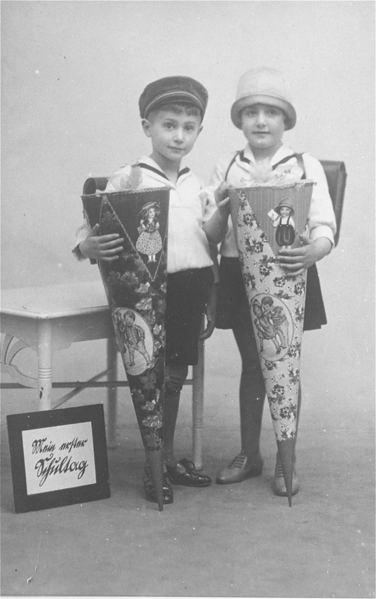 Studio portrait of the twins Leo and Celia Petranker holding candy cones on the first day of school.