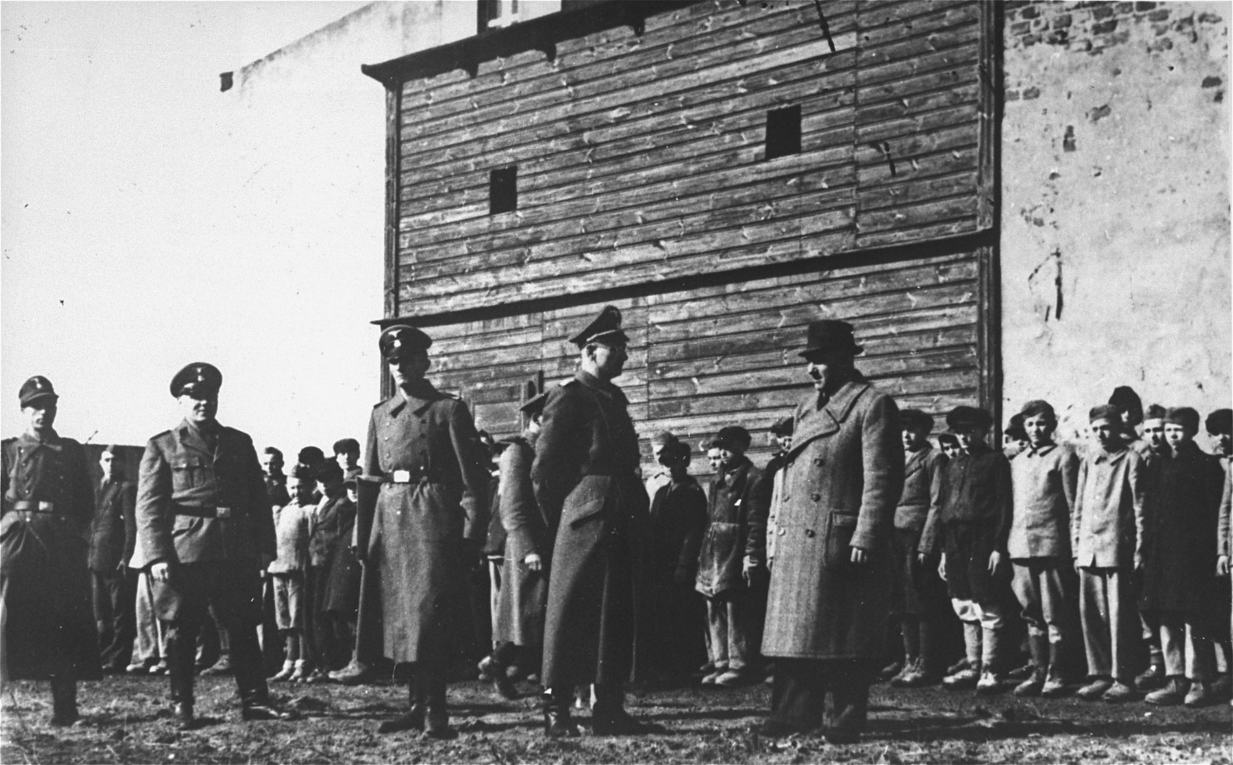 SS officers in front of a group of Polish youth and children during a roll call in the Jugendschutzlager Litzmannstadt.