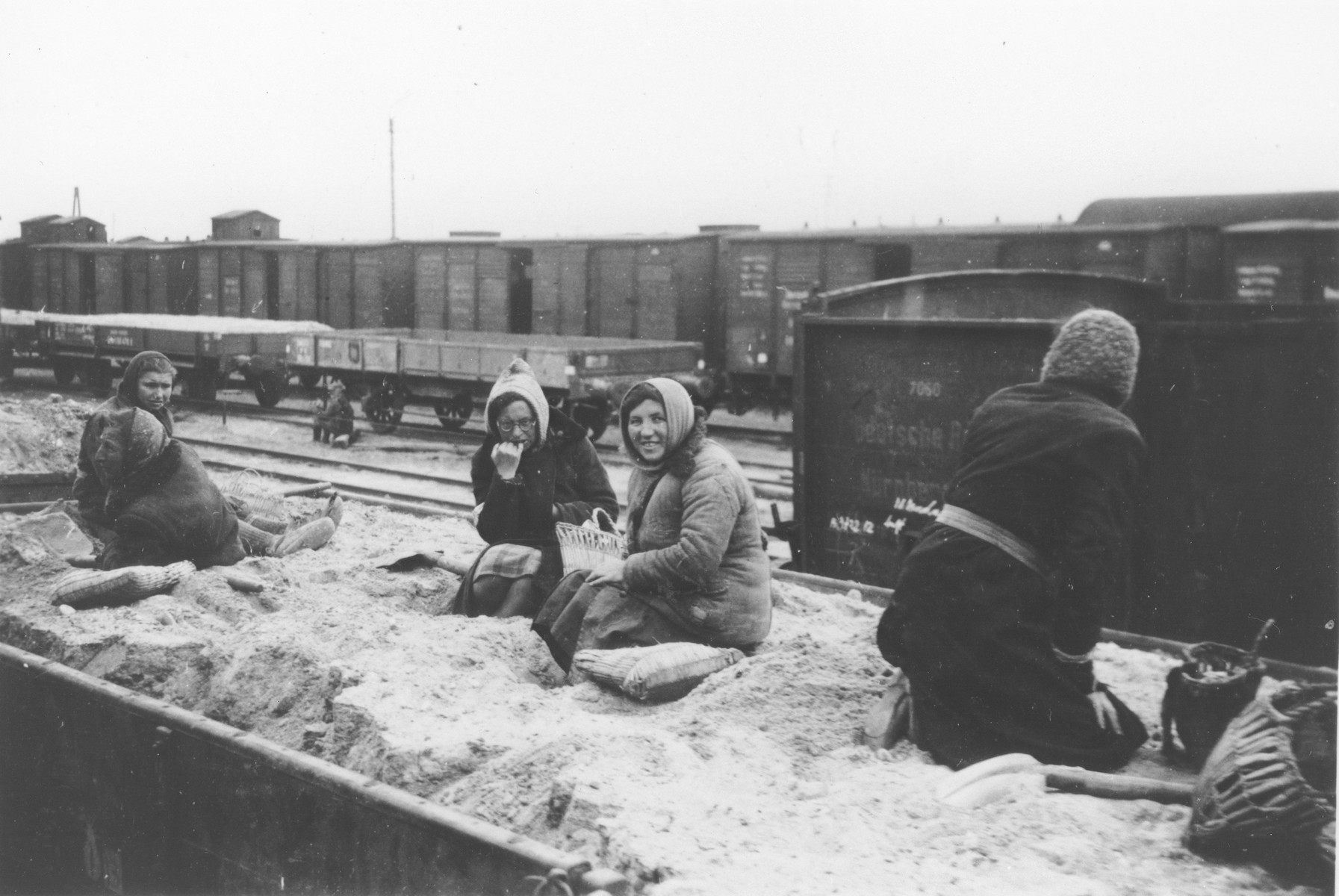 A group of Jewish women rest on top of a pile of dirt on a rail car where they have been shoveling.