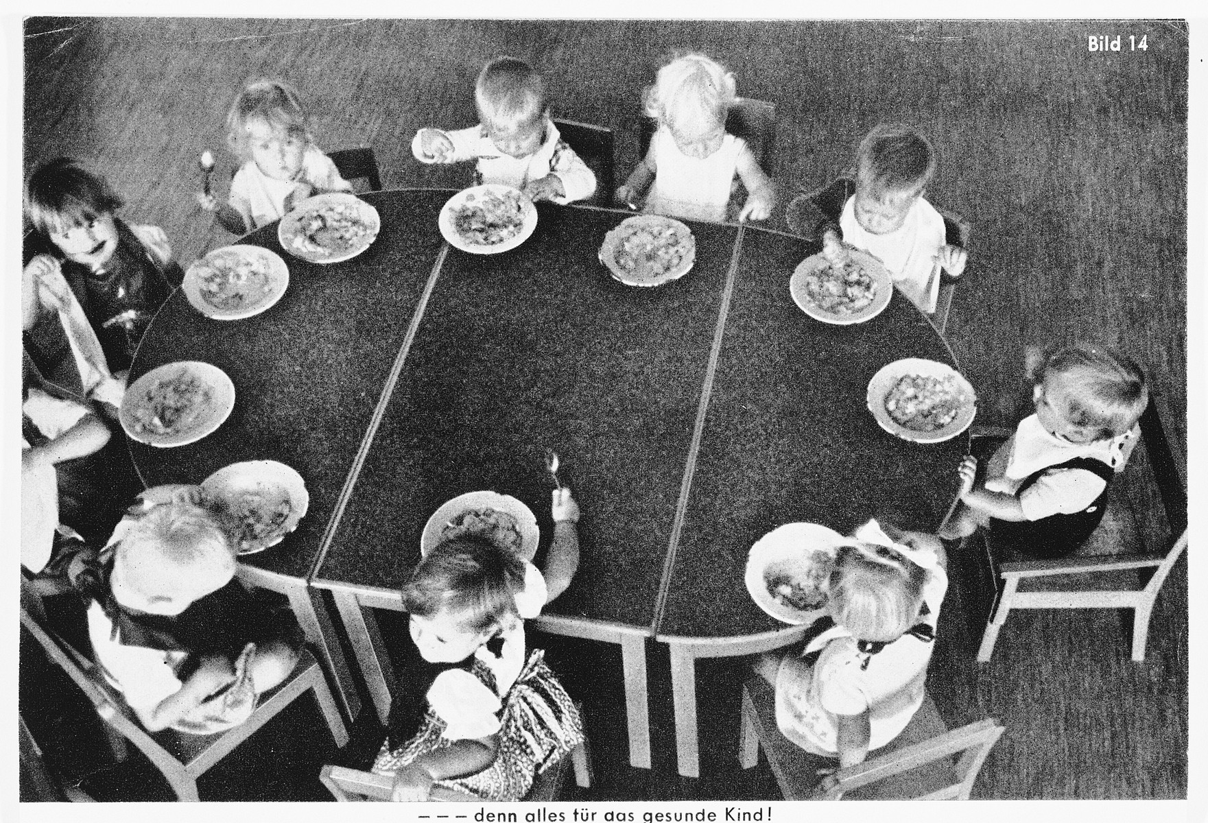"""German propaganda picture showing young German children sitting around a table and eating a meal.  The original caption reads: """"Everything for the healthy child."""""""