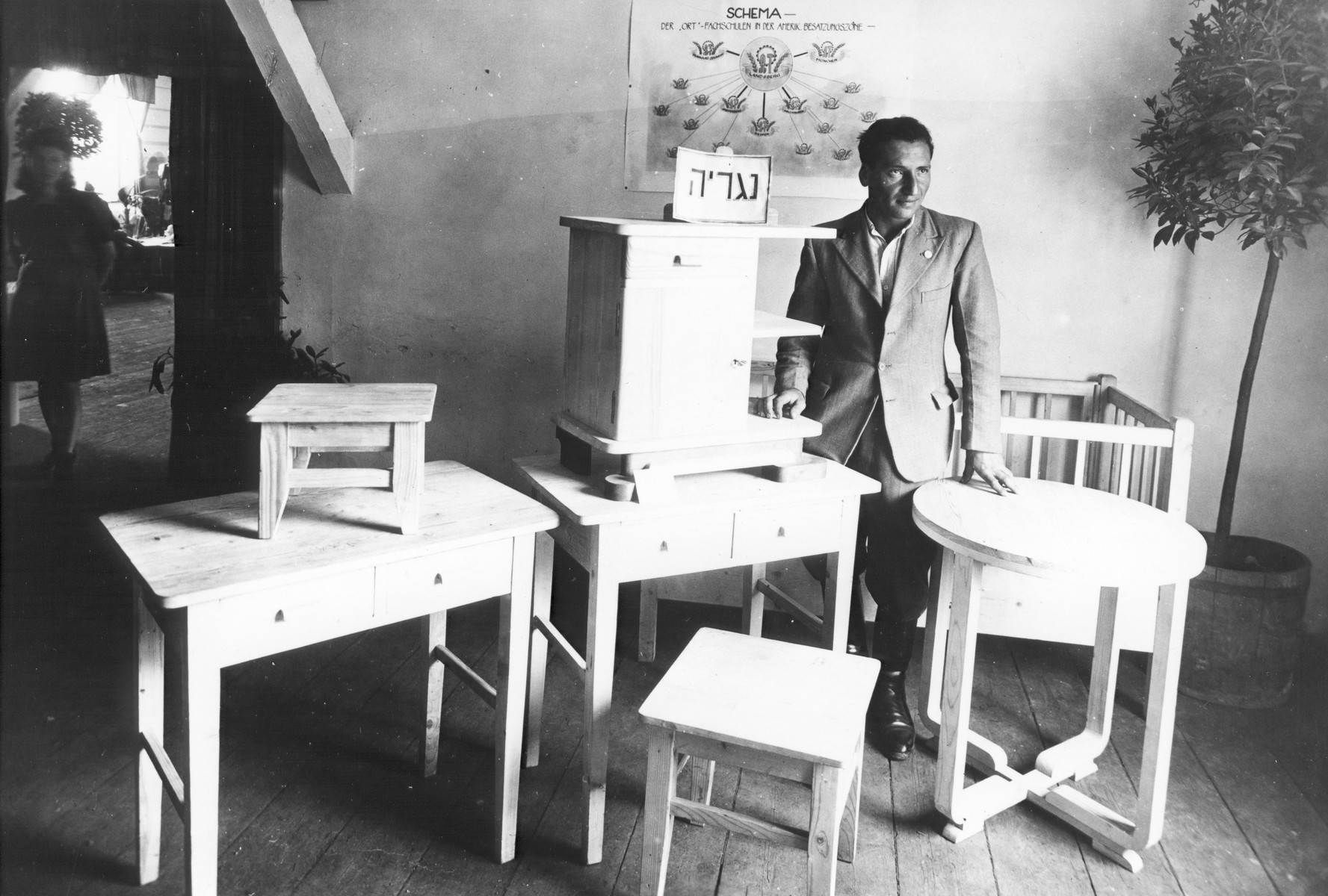 A man poses next to a display of furniture produced in an ORT carpentry workshop.