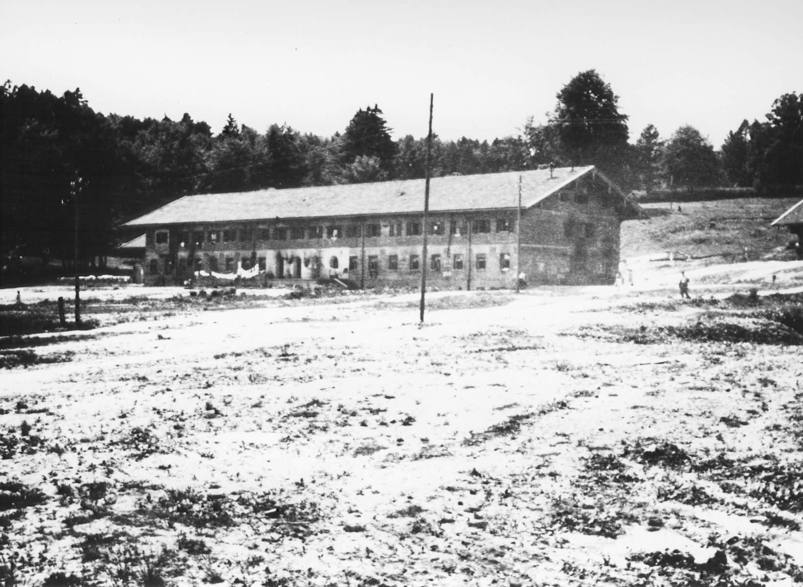 """Exterior view of the building which served as living quarters in the Feldafing DP camp.  The  building pictured is a """"Sturmblockhaus,"""" built in 1938 to house the Nationalsozialistische Deutsche Oberschule Starnberger See, established on the orders of SA-chief Ernst Roehm in 1934.  In April 1945, the school was dissolved and the building was repurposed to provide housing for displaced persons."""