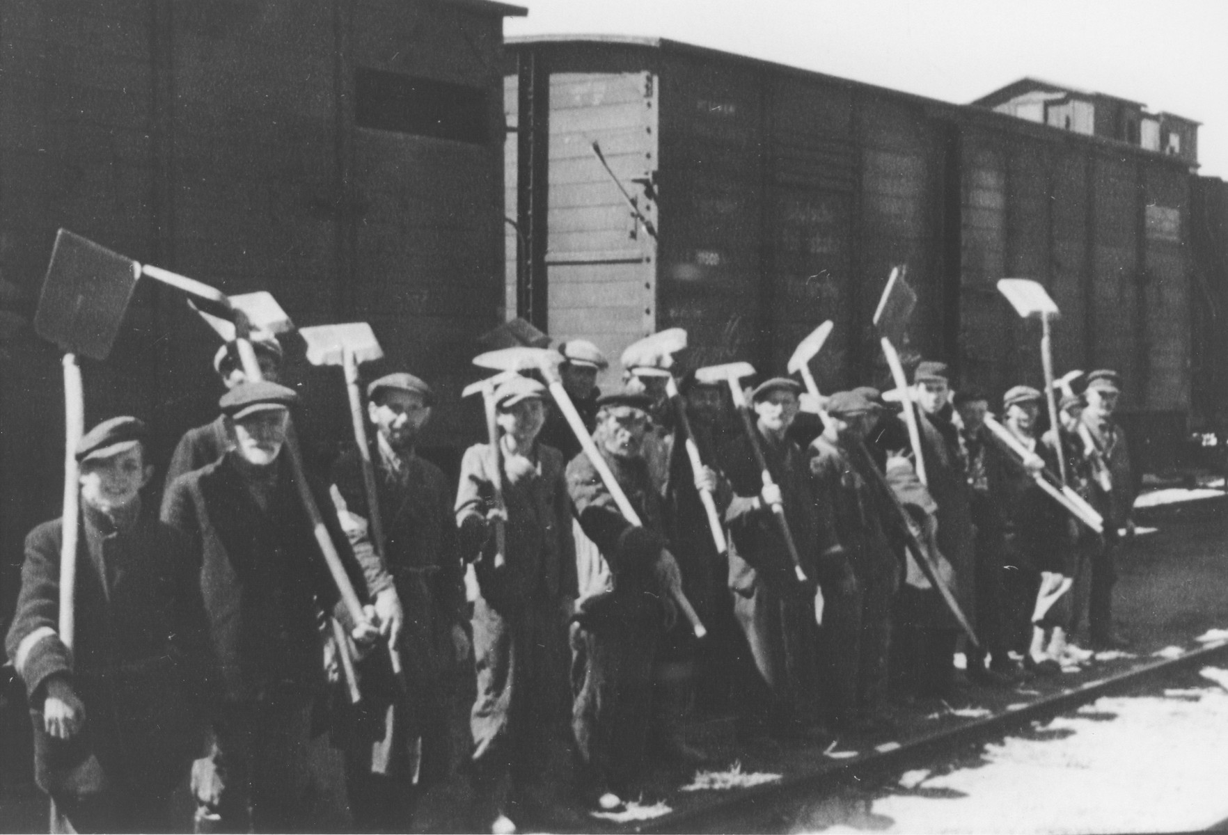 Jewish men and teenagers line-up with shovels in front of a train in an unidentified ghetto.