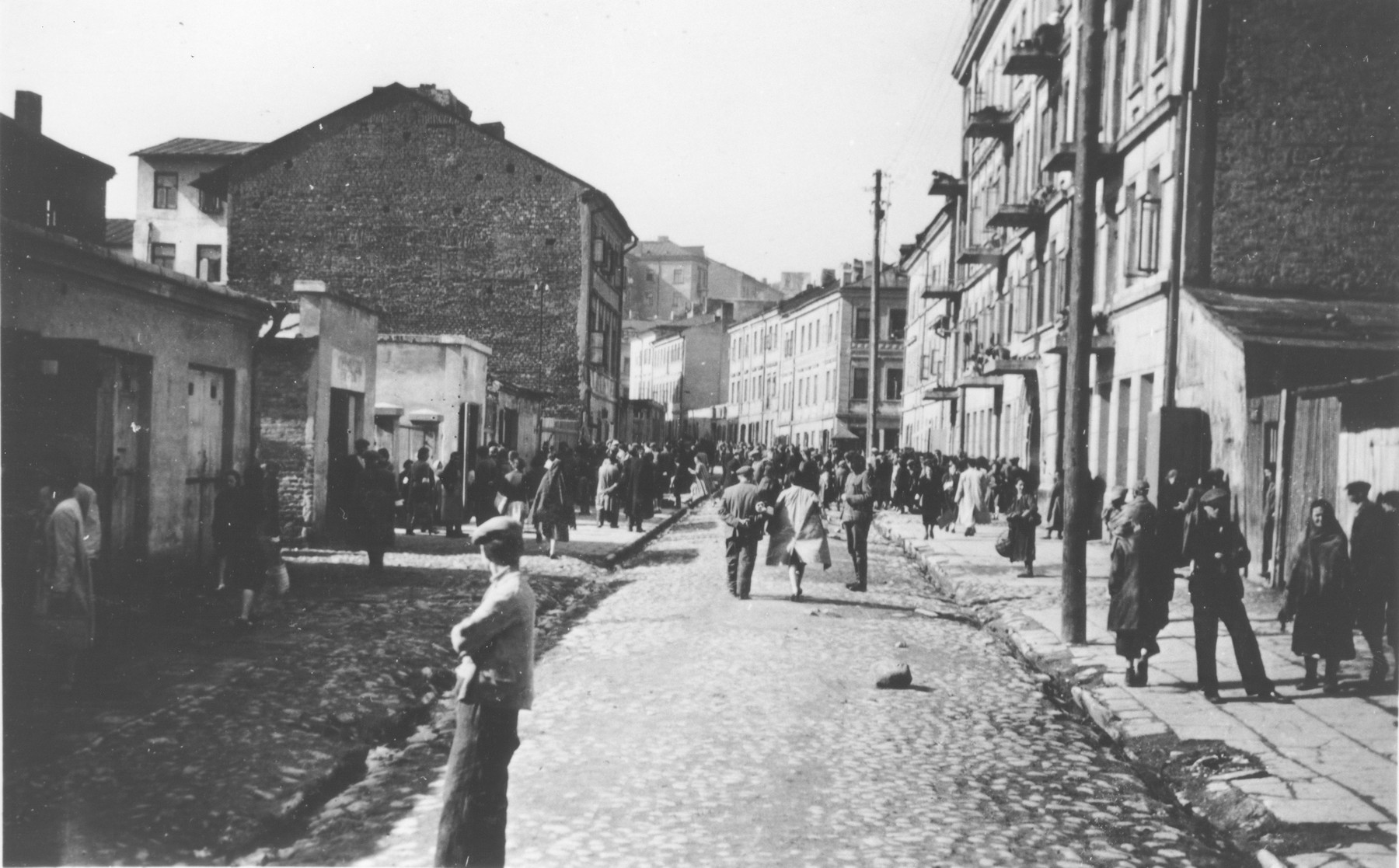Polish Jews wearing armbands walk down a busy commercial street in an unidentified ghetto.