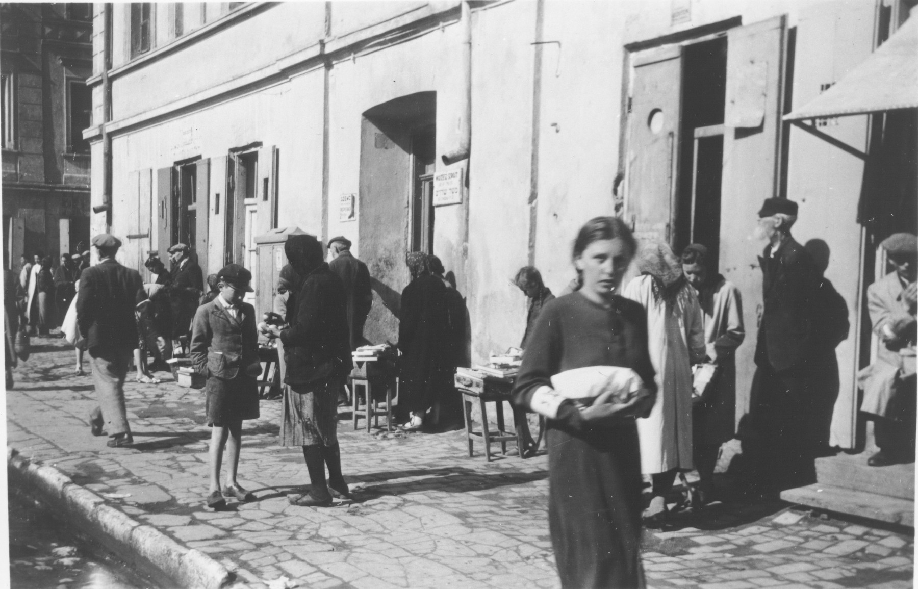 Polish Jews wearing armbands walk down a commercial street in an unidentified ghetto.