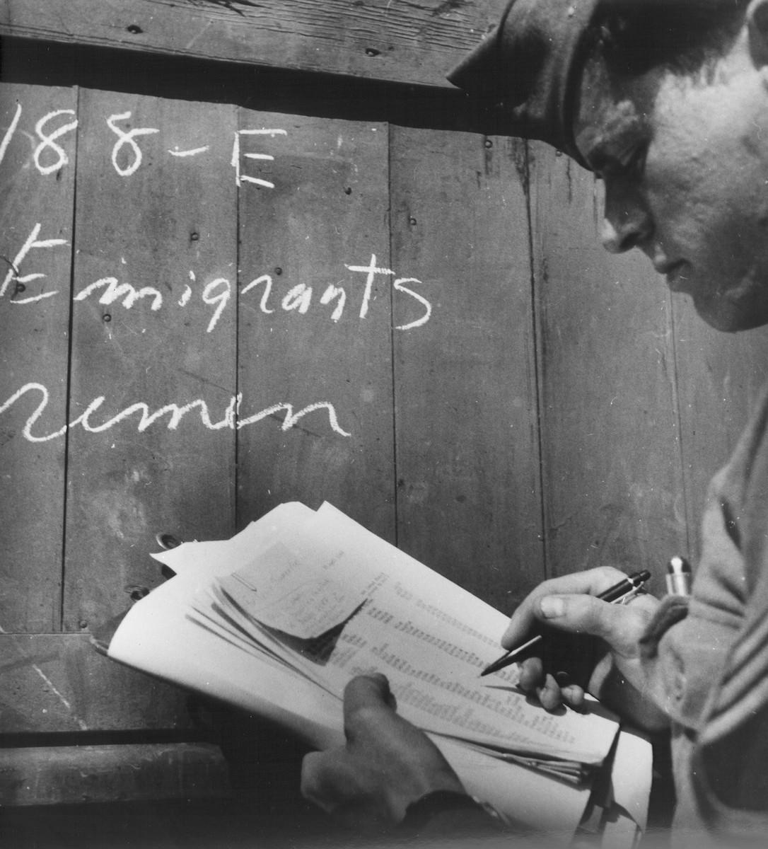An UNRRA worker checks an emigration list.