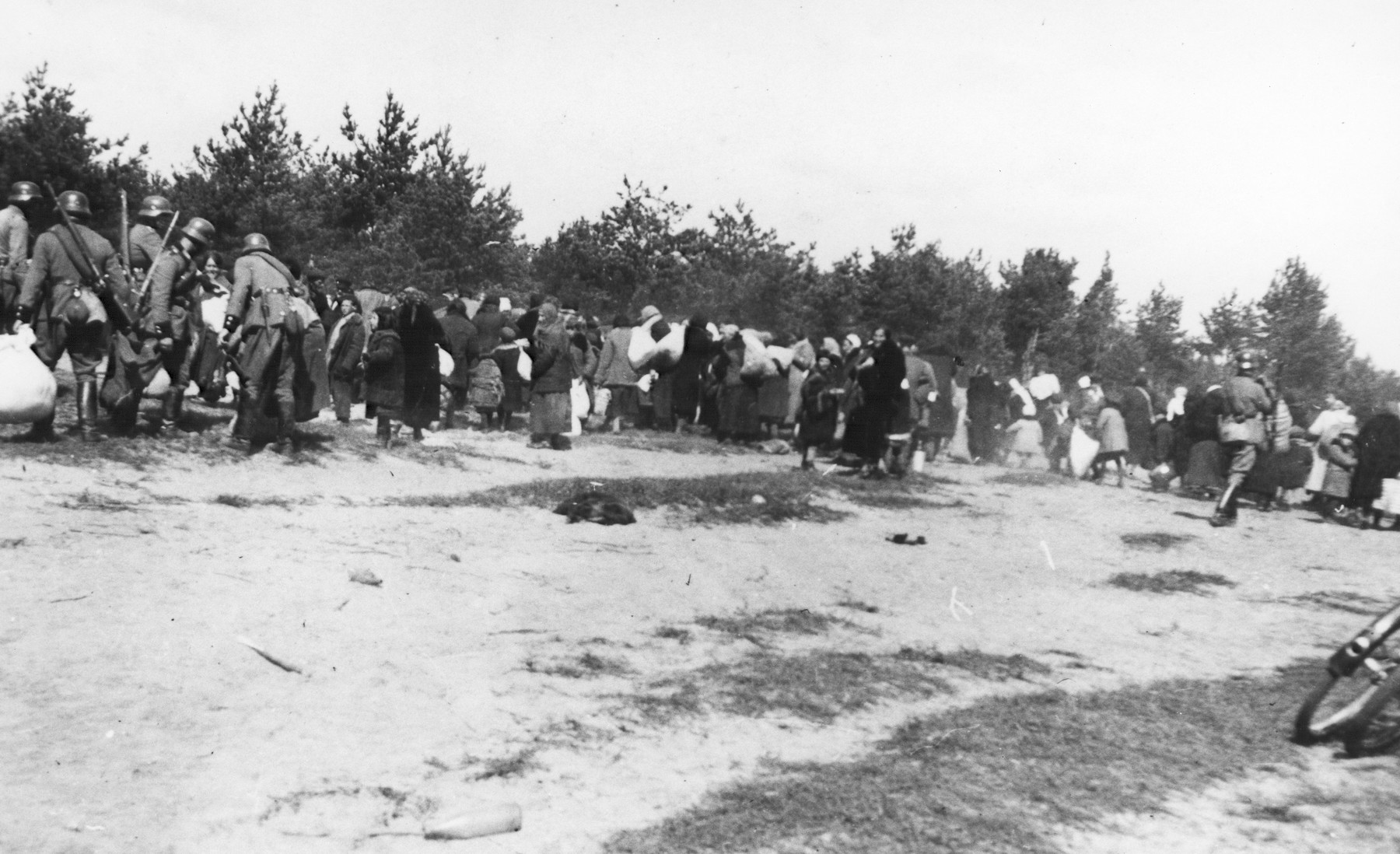 German and perhaps local gendarmes round Jewish elderly, women and children in a killing action in Lithuania.