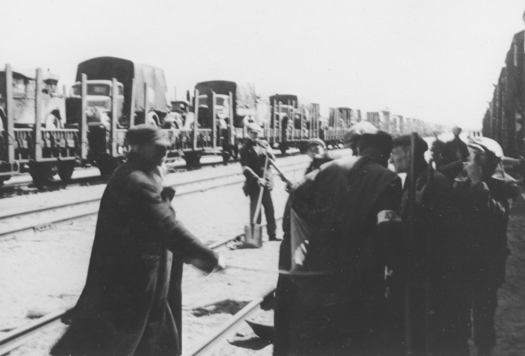 A group of Jewish men wearing armbands works at a railyard in Poland.  In the background is a long train carrying trucks.