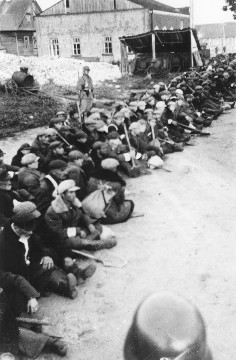Jewish men wearing armbands sit on the ground with shovels.  [They wre possibly rounded-up to dig mass graves.]