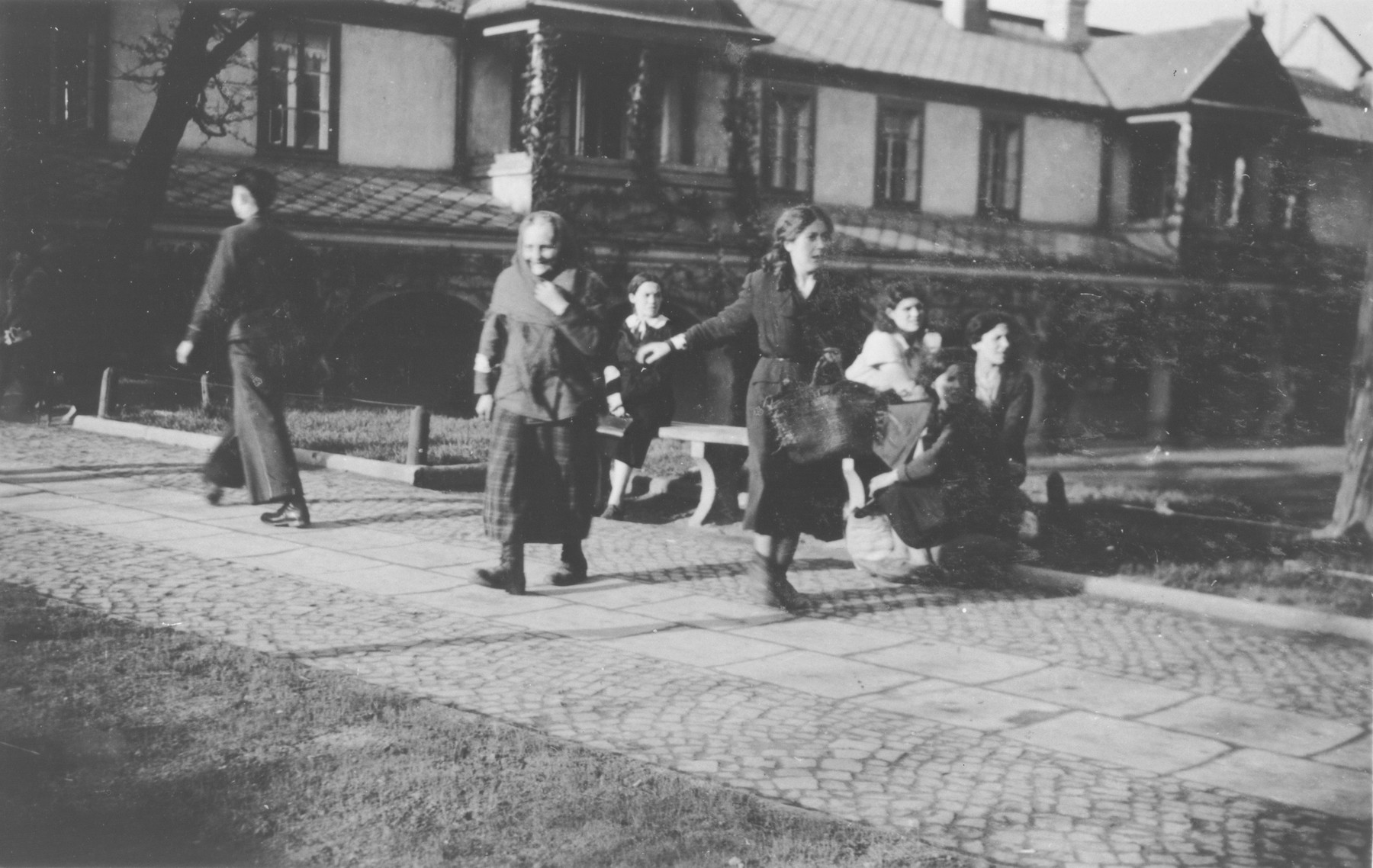 Men and women walk down a street and sit on benches in an unidentified ghetto.