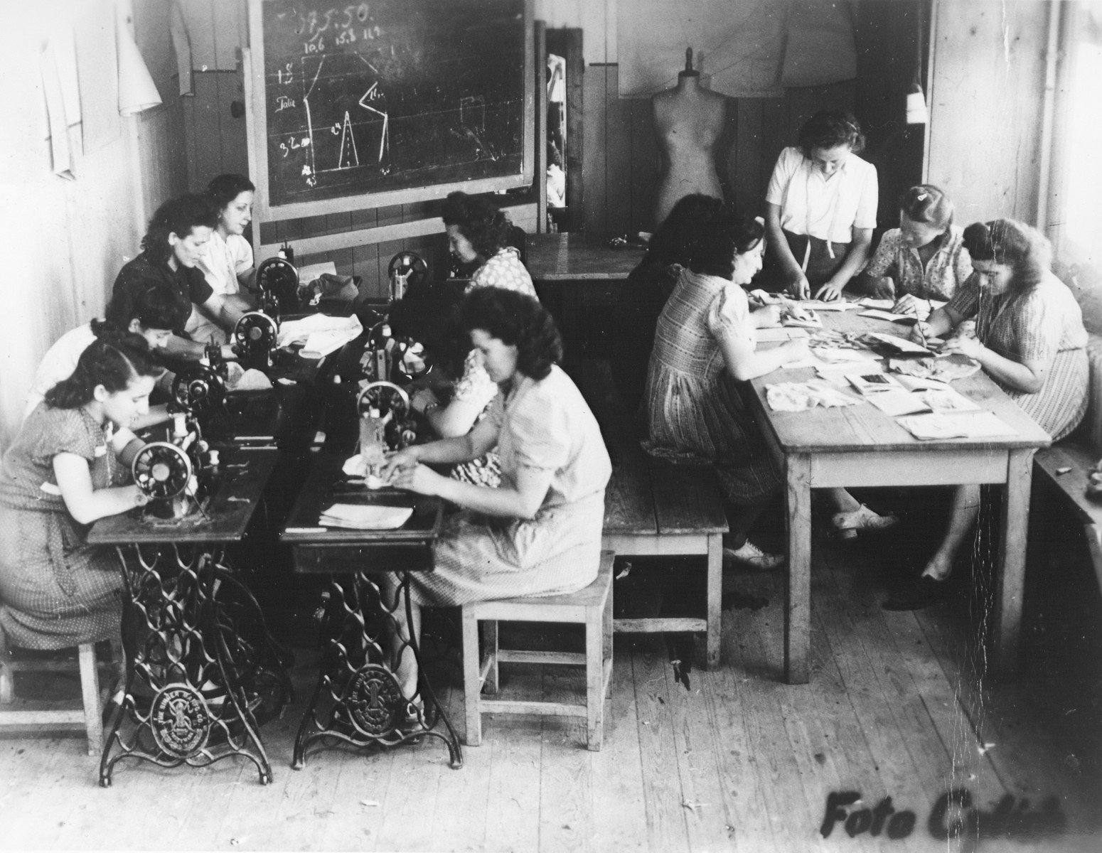 Women operate sewing machines in a tailoring workshop in the Feldafing displaced persons' camp.