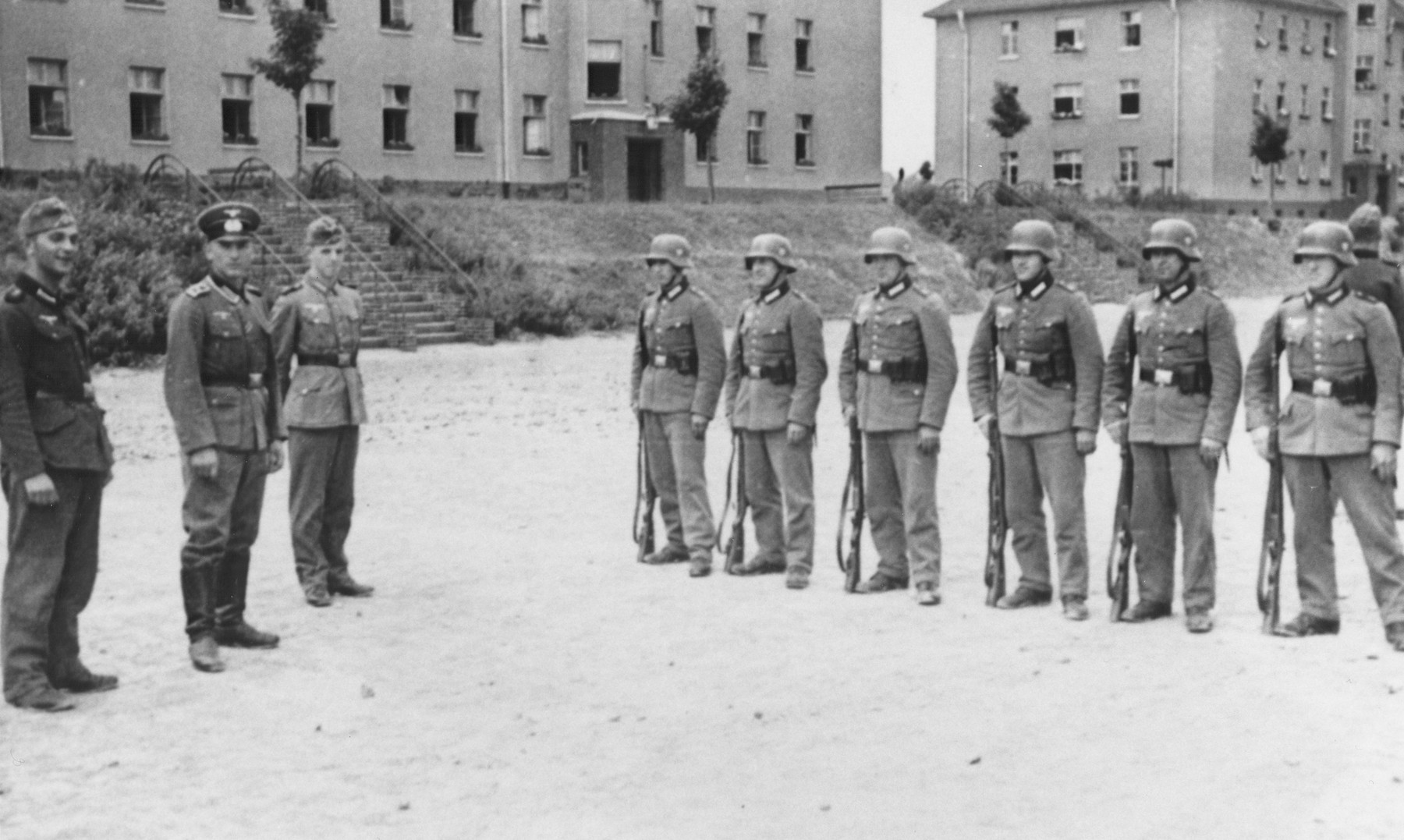 Members of Police Battalion 323 and probably Lithuanian auxiliaries stand at attention in a courtyard in front of the student dormatories of the University of Kaunas.