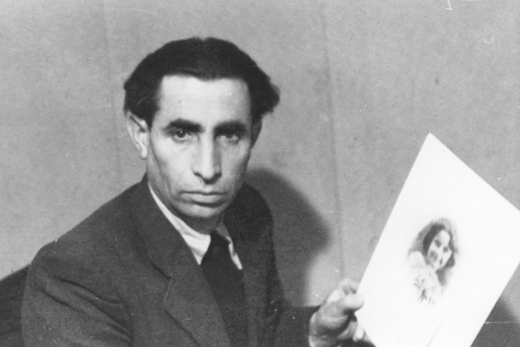 Survivor Hersh Portnoy holds up a photograph of his daughter Matle who perished during the war.