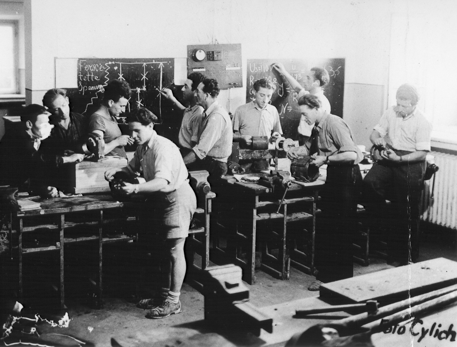 Jewish men participate in an ORT electrical motor winders training class in a machine workshop in the Feldafing displaced persons camp.  Pictured third from the left is Jacob Horowitz.
