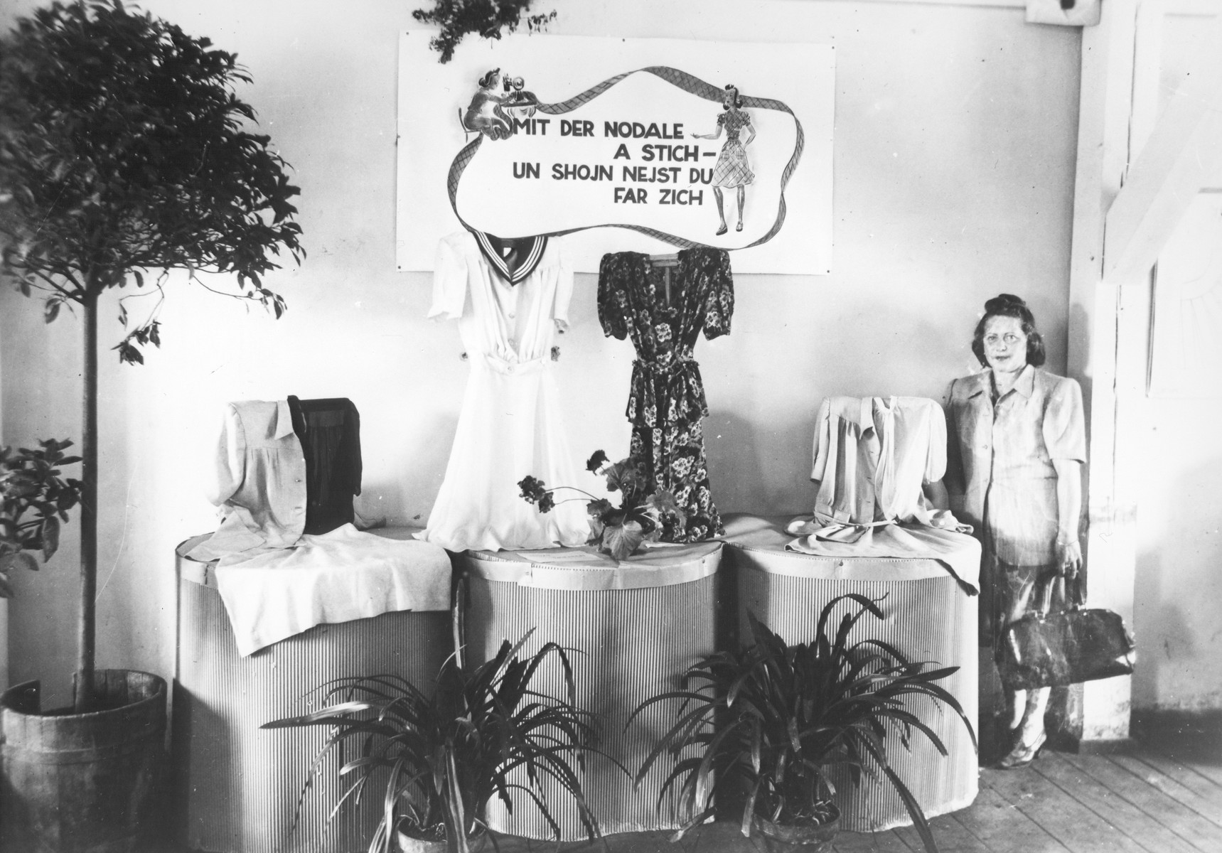 A woman poses by a display of clothing produced in an ORT-UNRRA school most probably in the Landsberg DP camp.