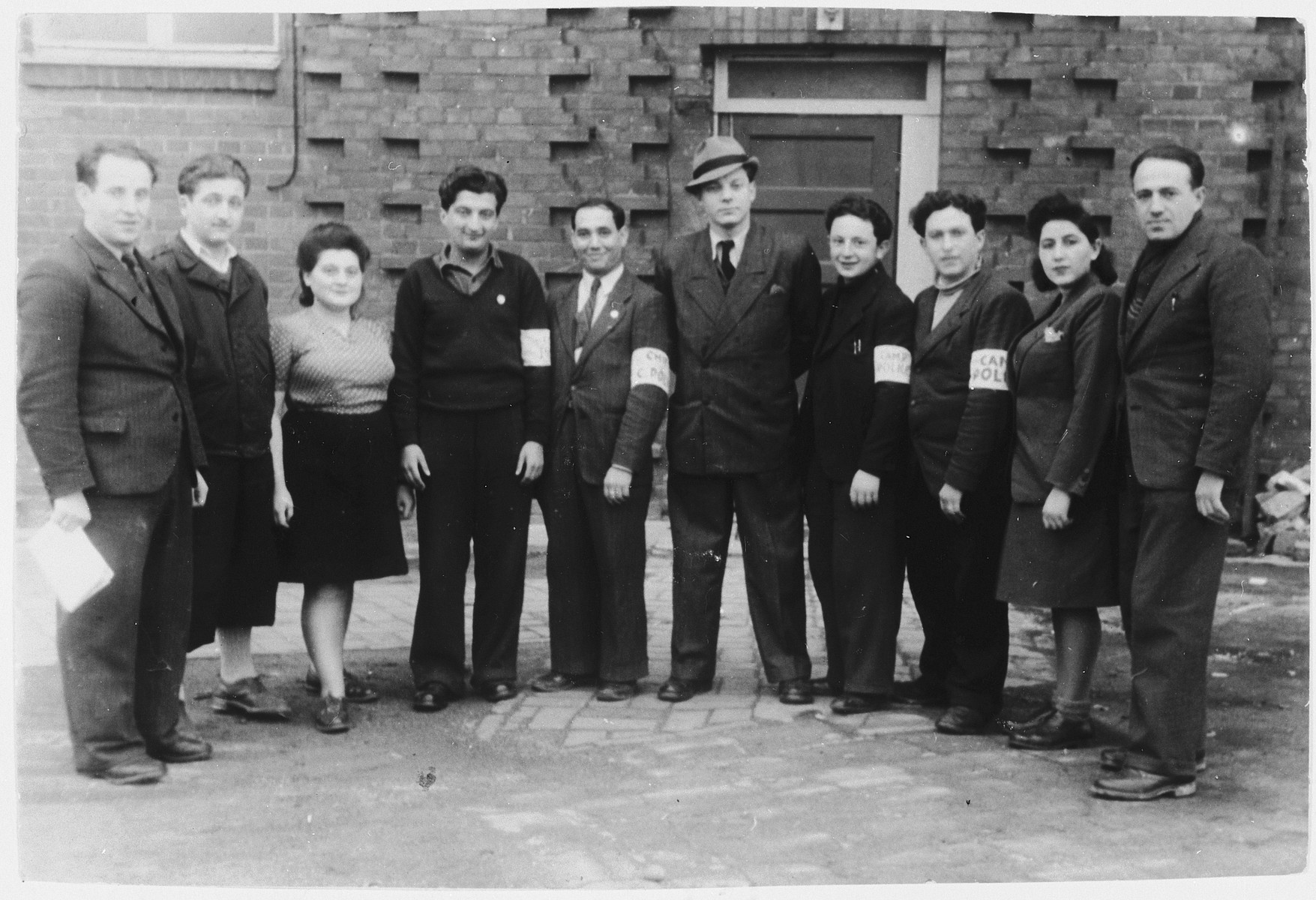 Group portrait of Jewish police in the Vinnhorst DP center.    Included in the photograph are Israel Zaks, Gutek Fiszel, Narwa and Chaim Katz.  Sam (Mulek) Pilcer is standing on the far right.  Henry (Henryk) Arfa is on the left.  Nadja Ring is the woman on the right and worked as the secretary.  Also pictured is Jacob Stefan Rue, head of the police force.  He is the standing in the center, wearing a hat.