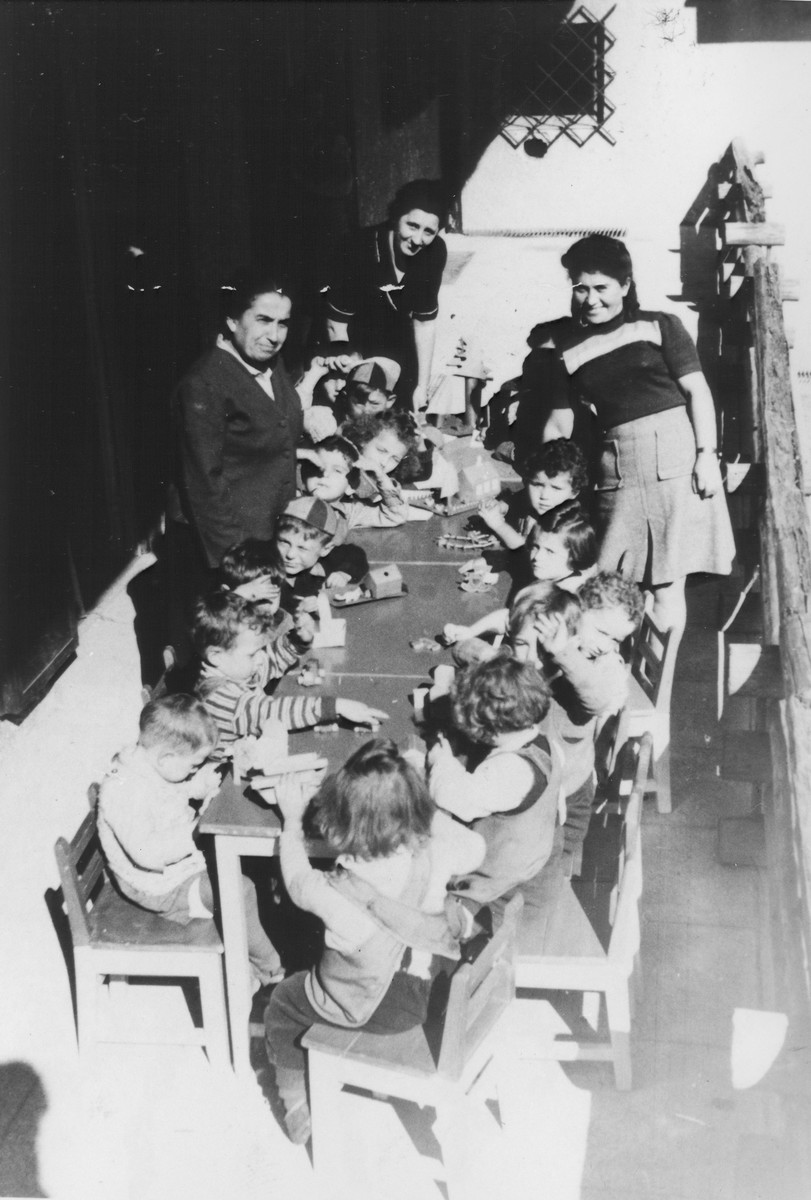 A kindergarten class sits around a table in the Feldafing displaced persons' camp.