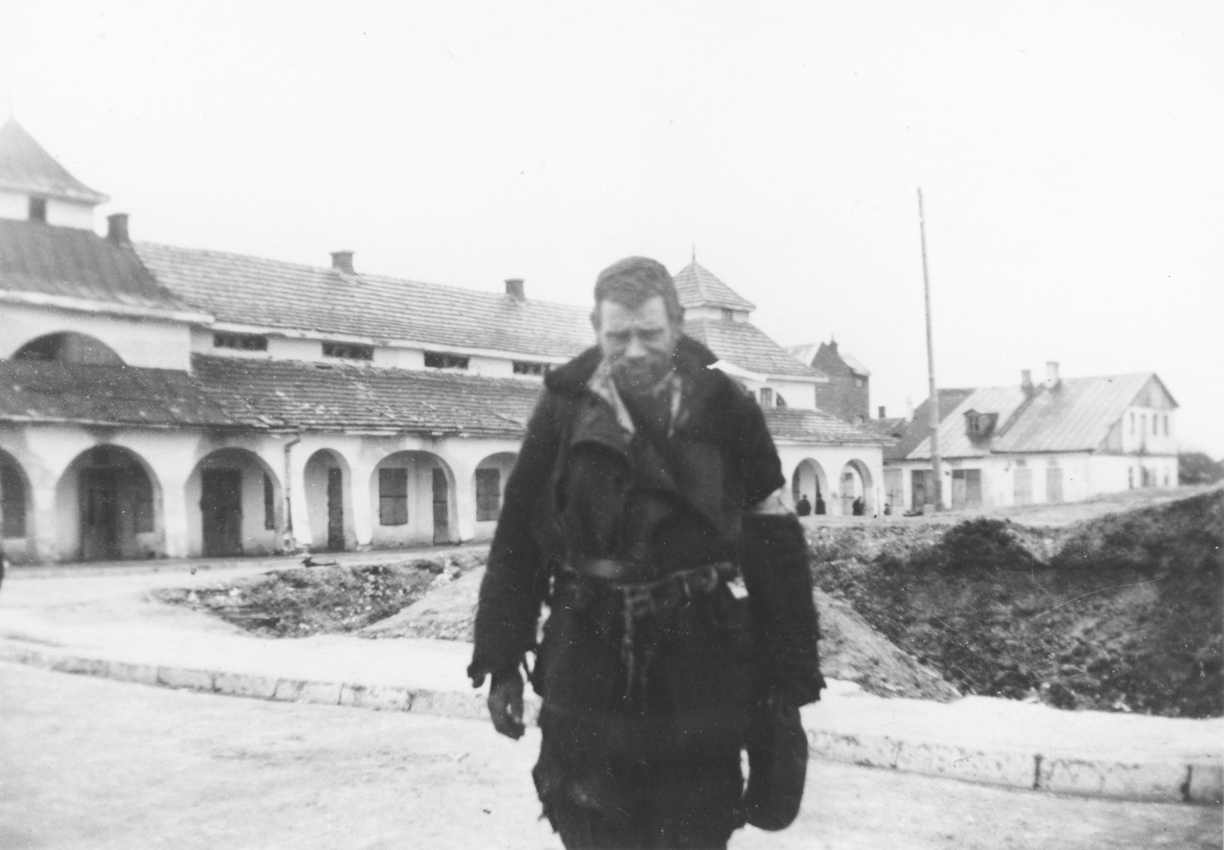 A destitute Jewish man in a torn jacket with an armband stands outside a large building in an unidentified town in Poland.