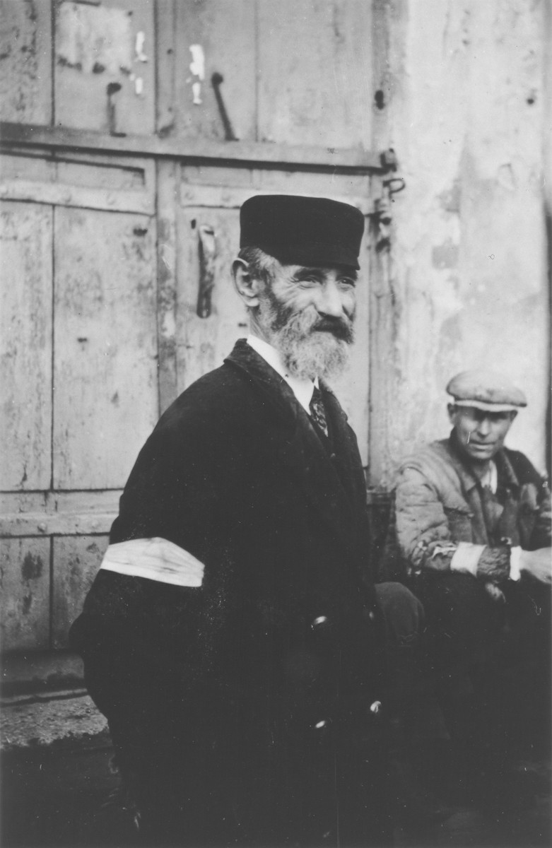 Close-up portrait of a bearded Jewish man wearing an armband in an unidentified ghetto.