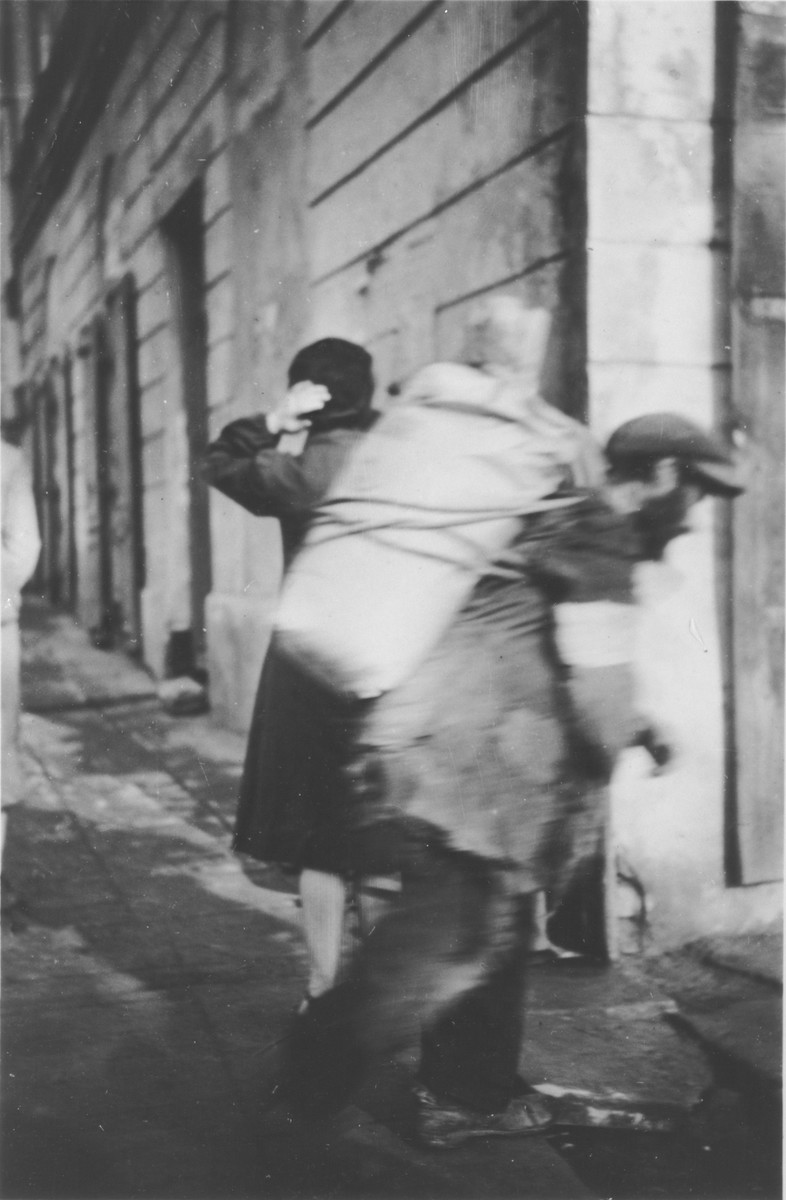 A porter carries a large bundle on his back in an unidentified ghetto in Poland.