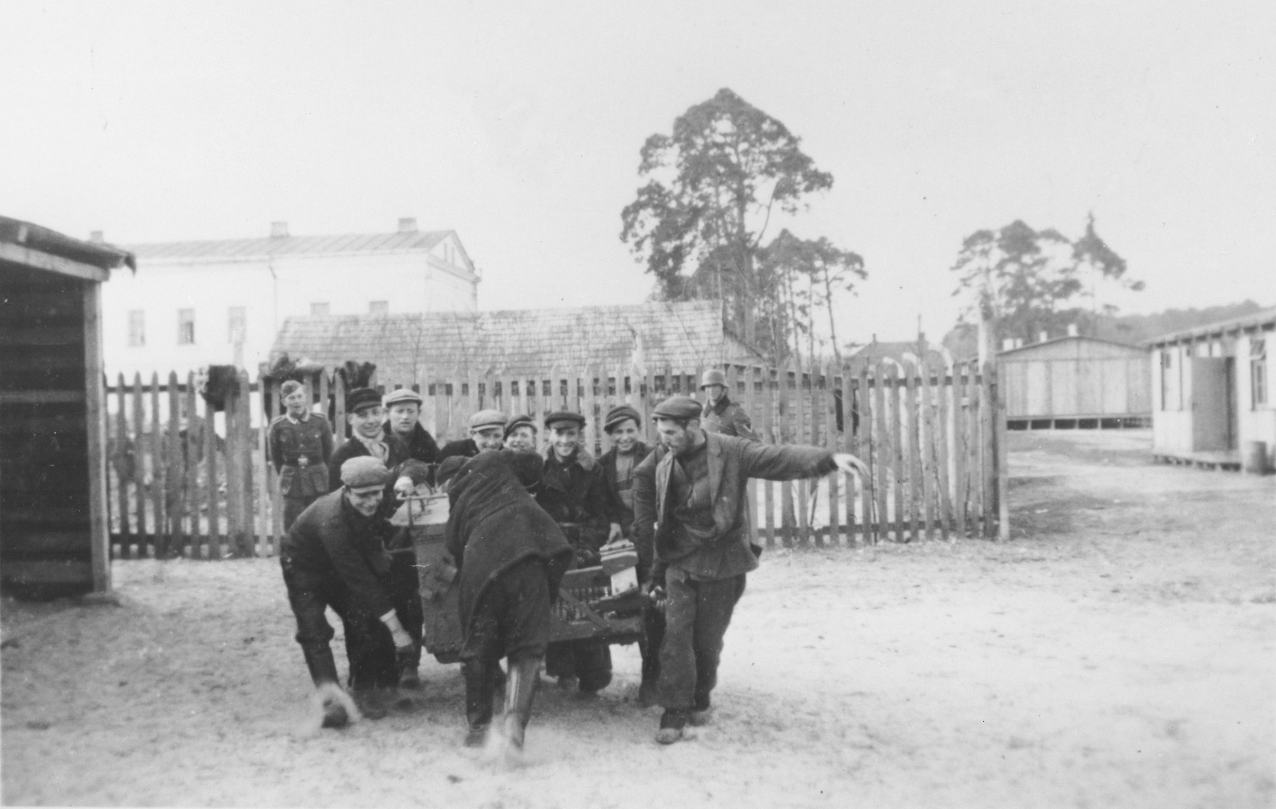 German soldiers supervise Jewish youth as they carry a heavy piece of either machinery or furniture.
