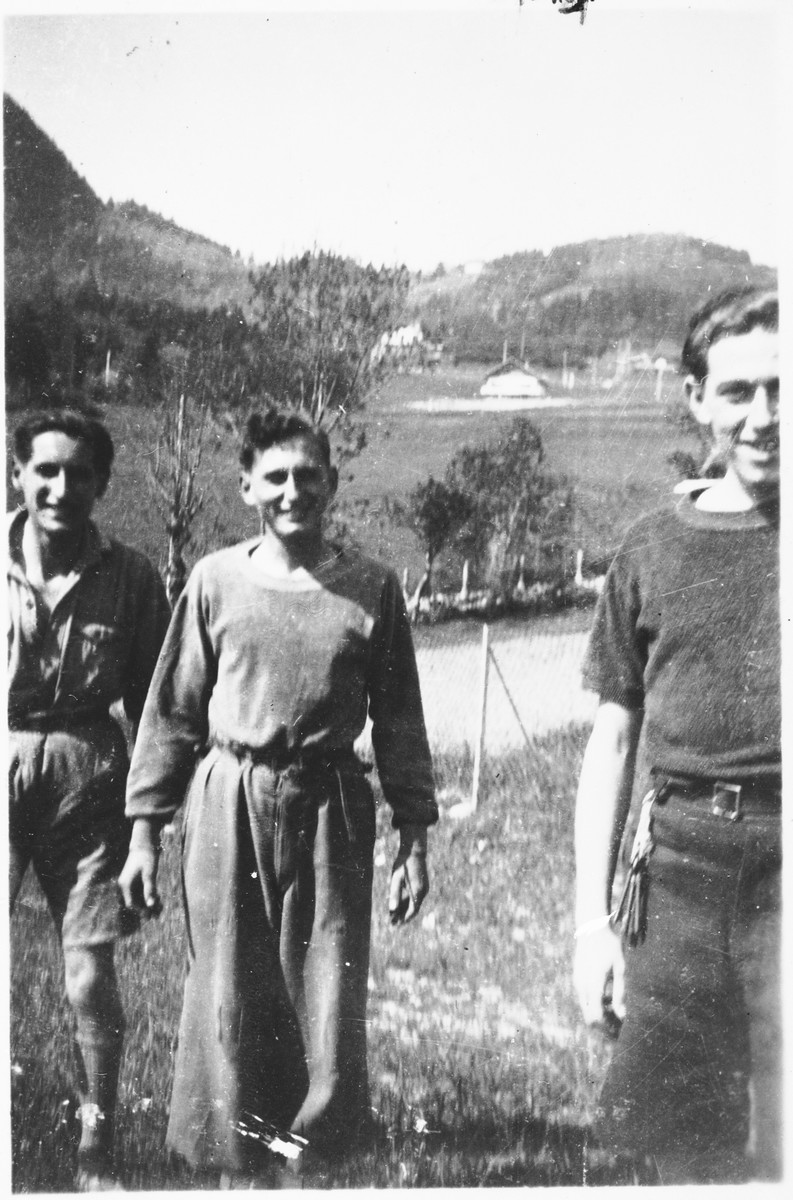 Three members of the Armée Juive walk through a field at their training camp in the Alps.  Pictured from left to right are: Isidore Rieger, Arthur Einhorn and Ado Michalovich.