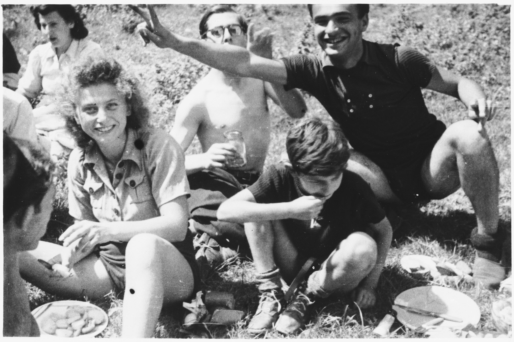 Members of Armée Juive enjoy a picnic in their training camp in the Alps.  Among those pictured are: Sabine Einhorn (left), Denis Hauser (front, right looking down), Joseph Fuchs (back center), Michael Latchiver (young boy) and Georges Schneck (back right).