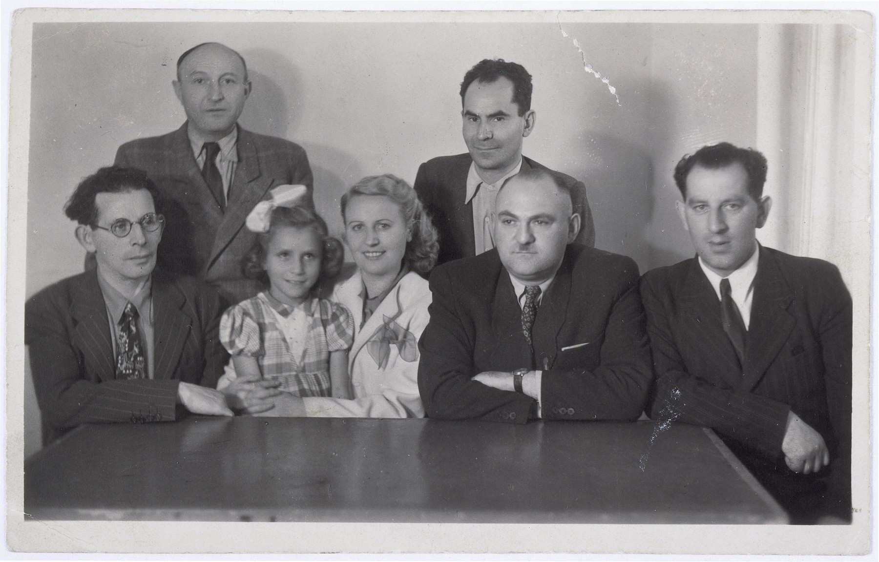 Group portrait of the committee that raised money to take Gitta Rosenzweig out of the Polish orphanage.  Gitta is seated on the lap of Ida Rosenstein.