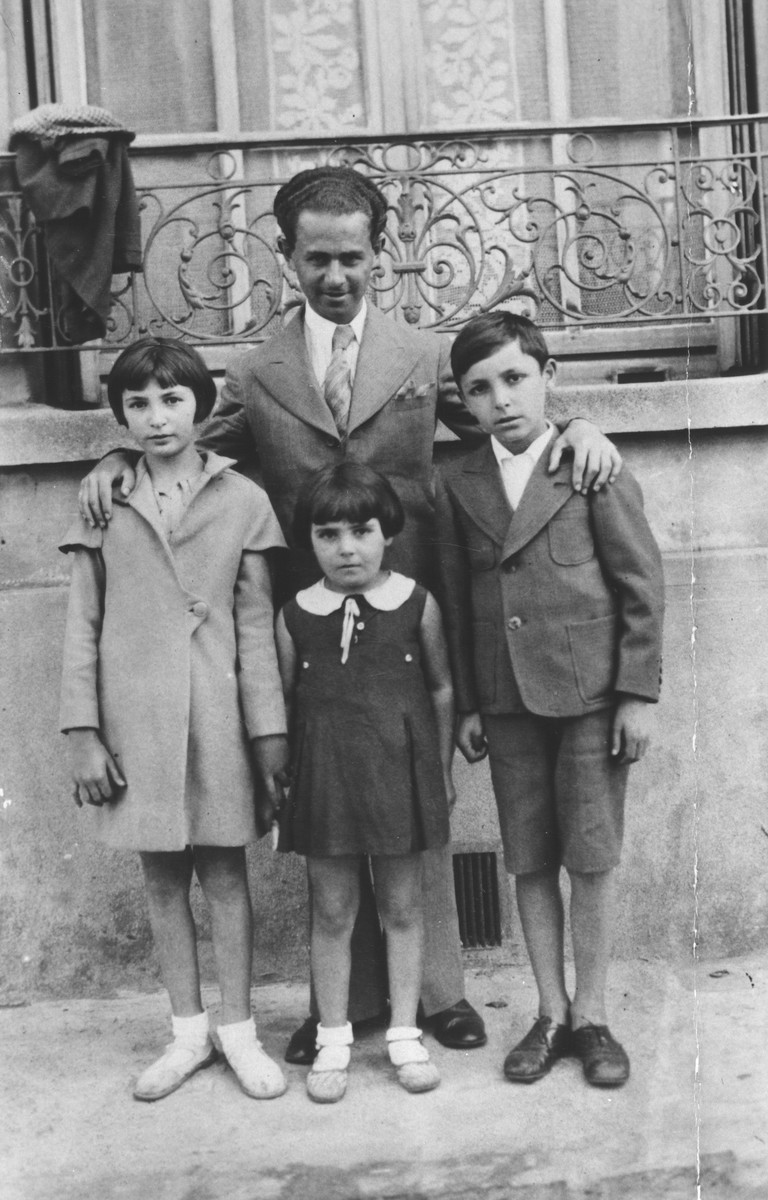 A father and three children stand outside their home on a street in France.