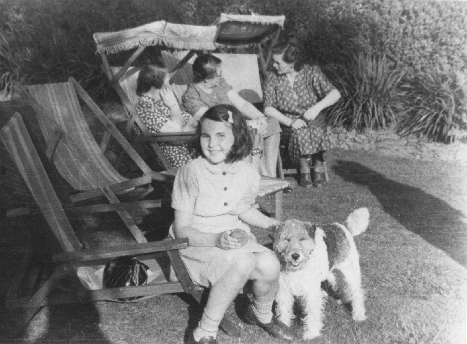 Helga Uszerowicz plays outside with a dog in Nottingham where she came on a Kindertransport.