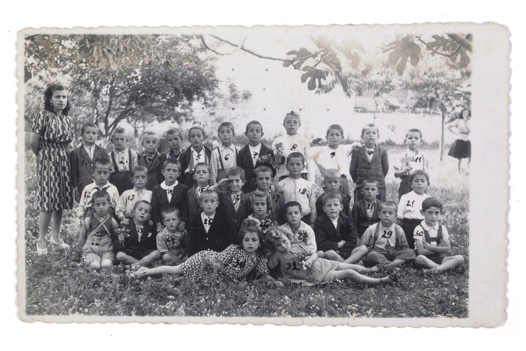 """Group portrait of Gavra Mandil's class at the Albanian school he attended in Kavaja.  Gavra is marked with a number 30 (first row, at the far right).    This picture was taken shortly after the Mandils arrived in Kavaja.  Gavra, who had attended first grade in a different location posing as a Christian, was hiding as a Moslem in Kavaja.  When called by his new teacher in Kavaja to go to a religion class, six-year-old Gavra became confused and did not know whether to attend the Christian or Islamic class.  It was only after the teacher scolded him, saying """"Ismail, what is the matter with you?"""" that Gavra remembered his new religious identity."""