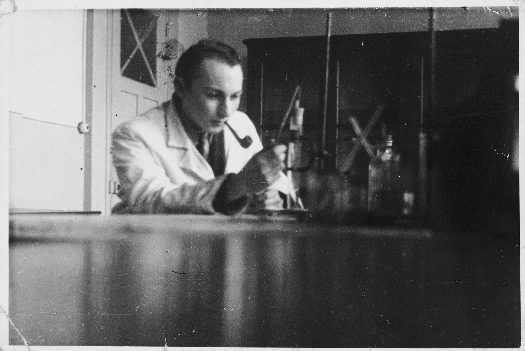 Toto (Otto Giniewski, later Etan Guinat), a Zionist activist and leader of the Armée Juive, works at his laboratory at the University of Grenoble.  His laboratory served as his headquarters where he could hide illegal items such as blank cards,stamps etc. needed for the underground and also receive messengers from all parts of  France.   The photo was taken by Jacques Dubois, a student who shared his office.