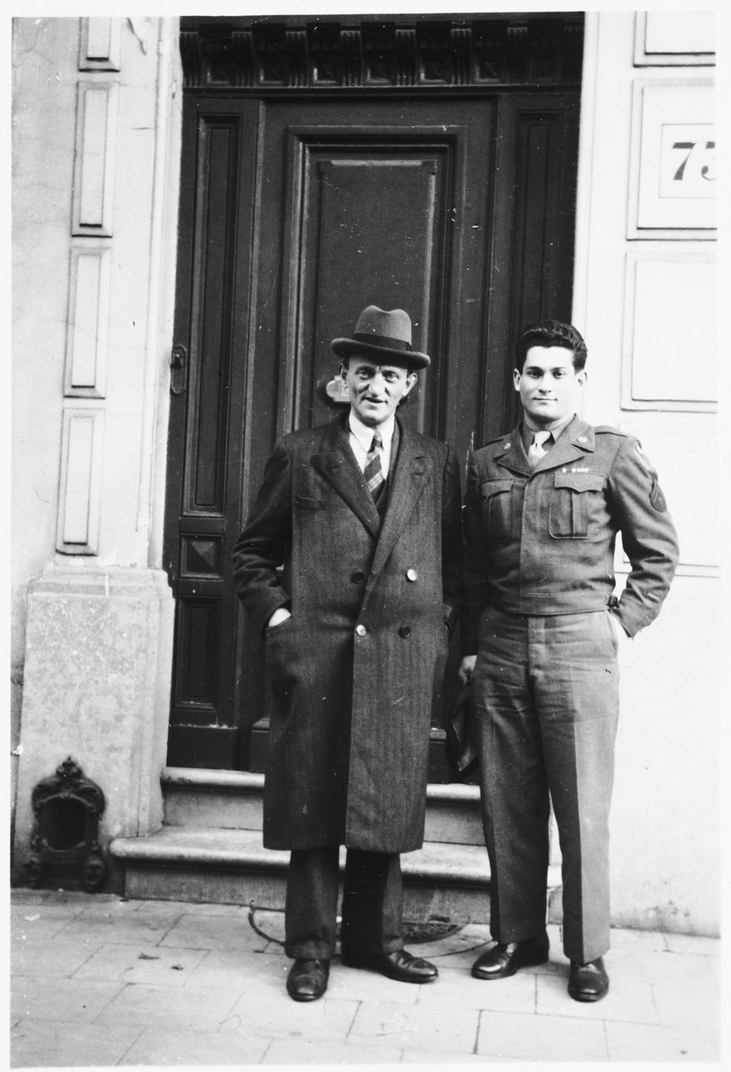 Jewish Brigade soldier Arthur Einhorn poses with his father at the entrance to a building during their first postwar reunion.