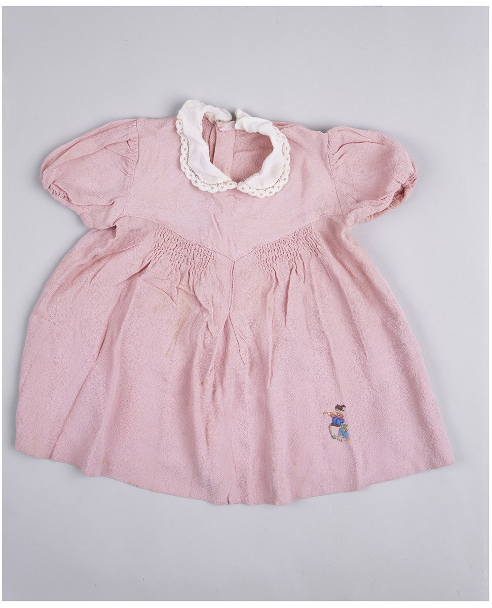 """A pink dress with a white """"peter pan"""" collar worn by the donor's sister, Lela, who was killed in a German bombing raid on Sarajevo."""