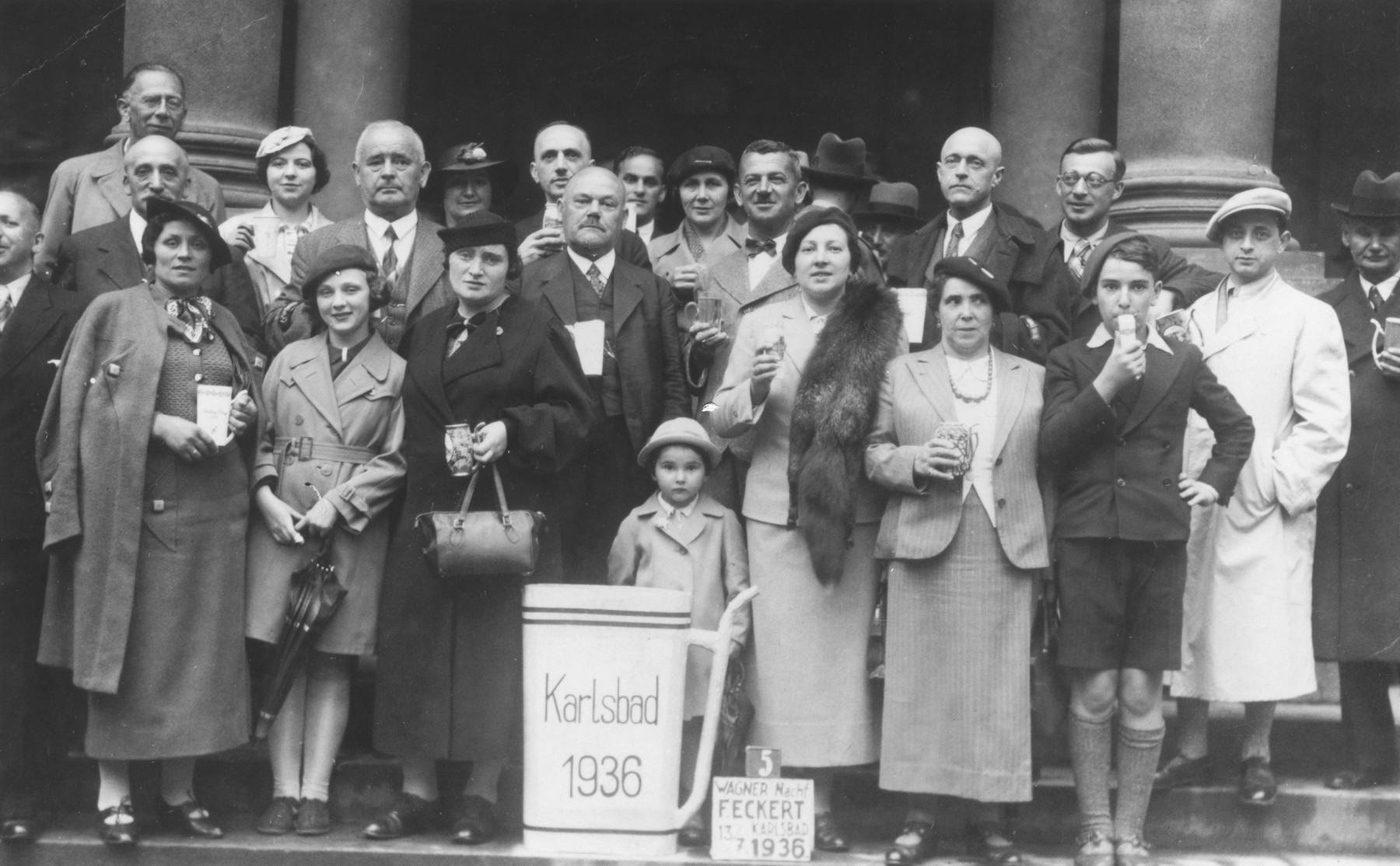 The Uszerowicz family poses with glasses of mineral water along with other patrons of a spa in Karlsbad.