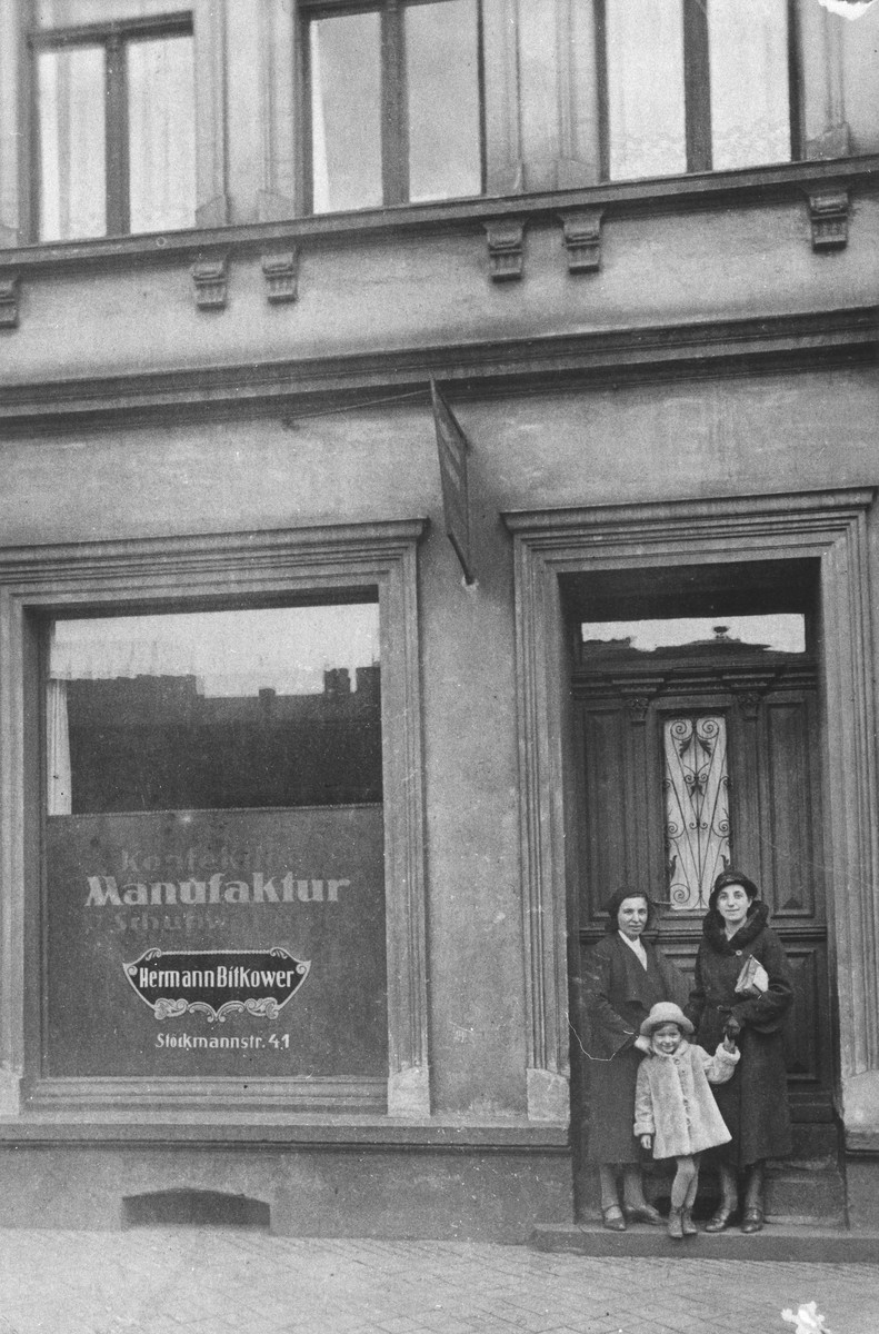 Two women and a child stand outside the entrance to a manufacturing business.