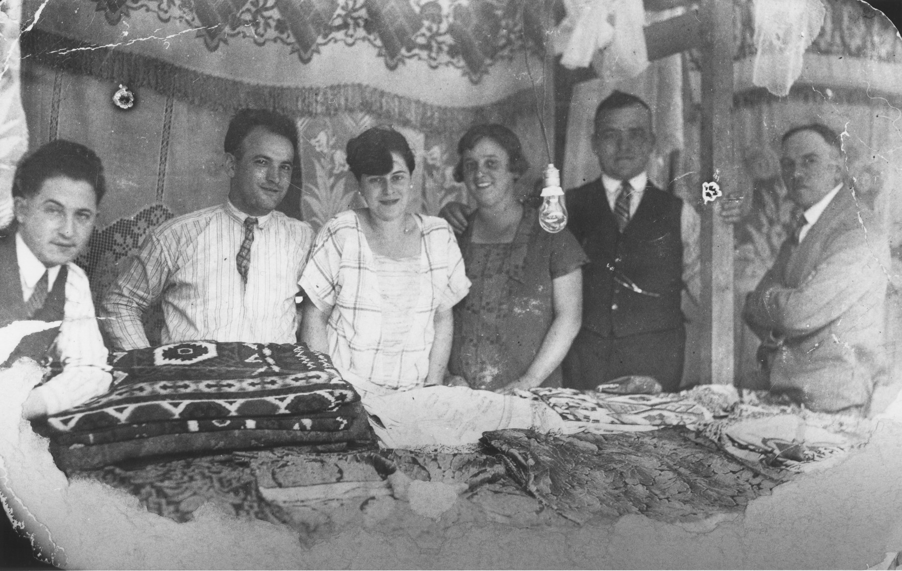 Jakob Uszerowicz and a group of friends examine embroidered and patterned fabrics.