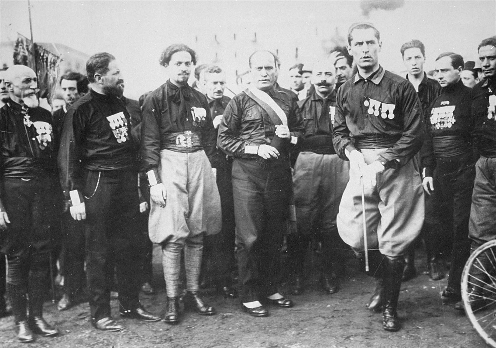 "Mussolini poses with comrades in the Black Shirts.  Pictured on the far left is Emilio De Bono. De Bono was nominated as Director General of the Police (Direttore Generale della P.S.) on 11 November 1922. His title was changed to ""Intendente Generale di polizia"" on 11 November 1923 and then on 20 December 1923, his title became ""Capo della Poliza"" or Head of Police."
