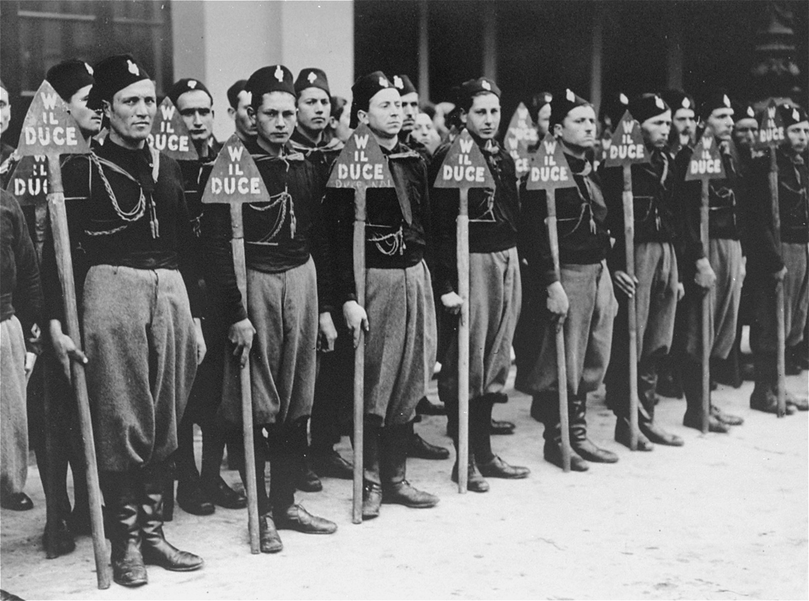 A unit of Italian blackshirts stands at attention holding spades during a fascist demonstration.