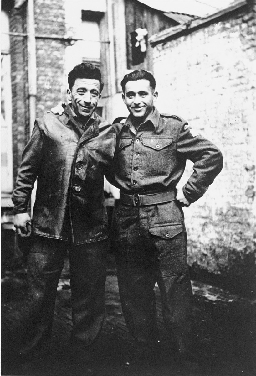 A Jewish Brigade soldier poses in a courtyard in Antwerp, Belgium with one of the members of the Kibbutz Buchenwald hachshara who is waiting for passage to Palestine.